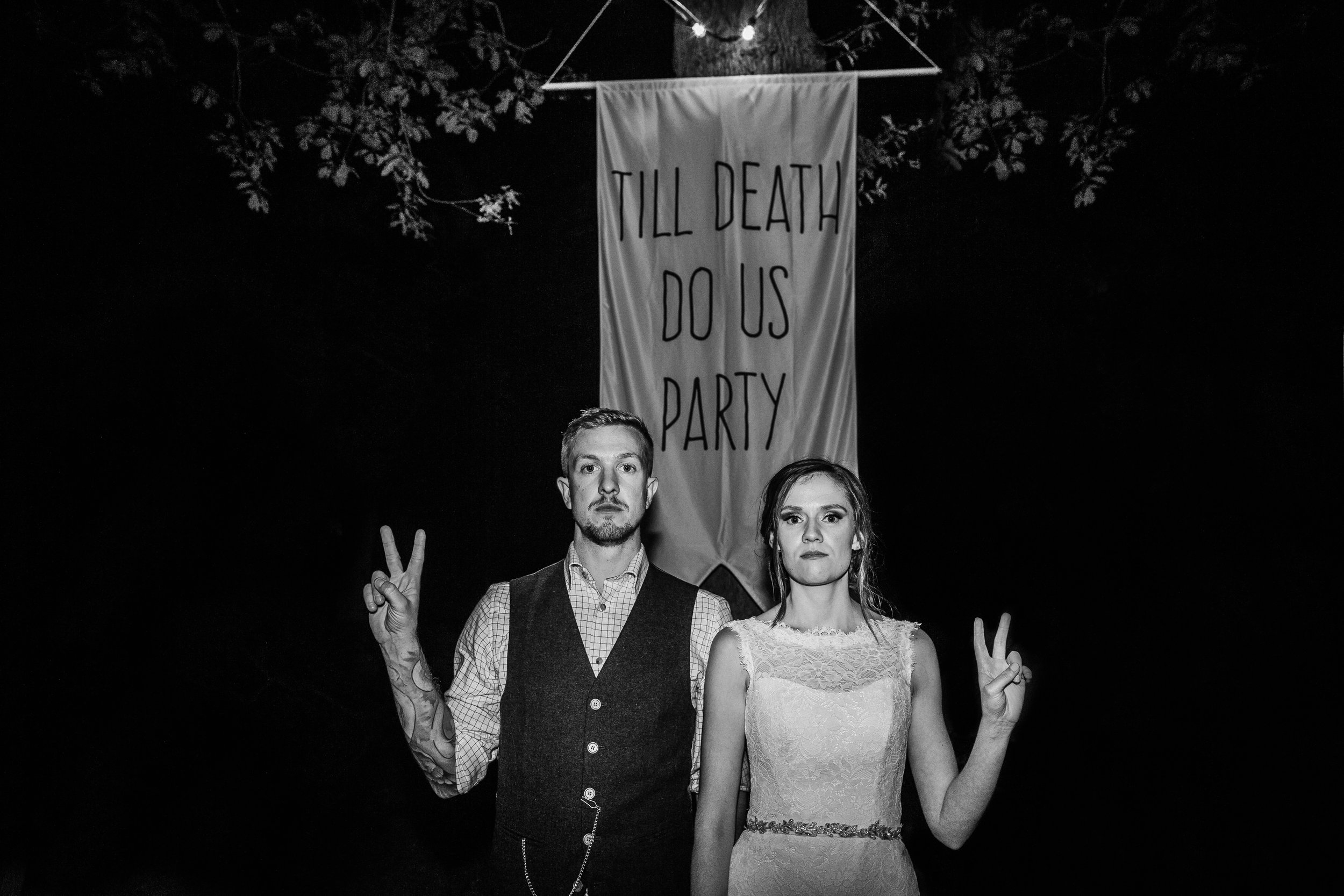 a bride and groom posing in front of a banner saying till death do we party at Enchanted weddings birmingham