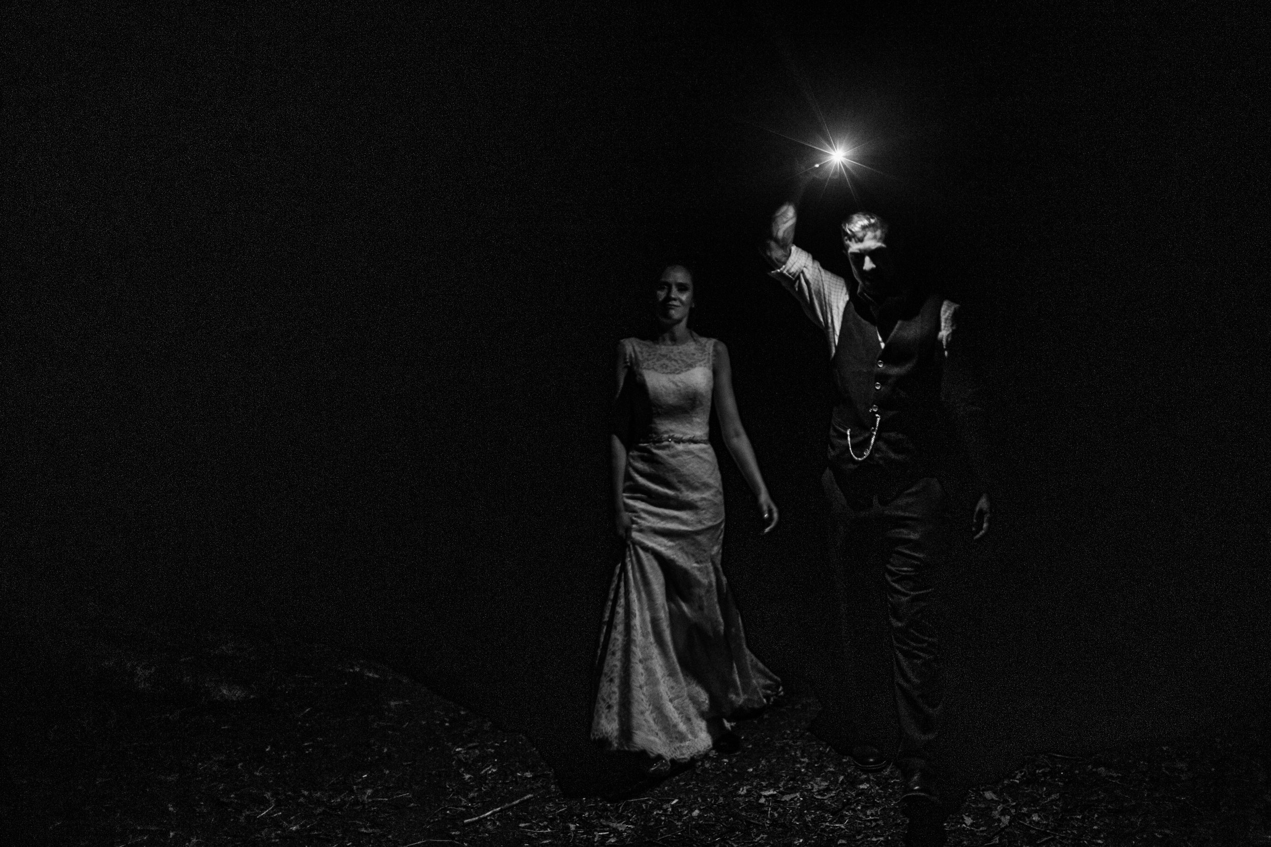 a bride and groom in the dark leading the way with an iphone torch at enchanted weddings birmimgham