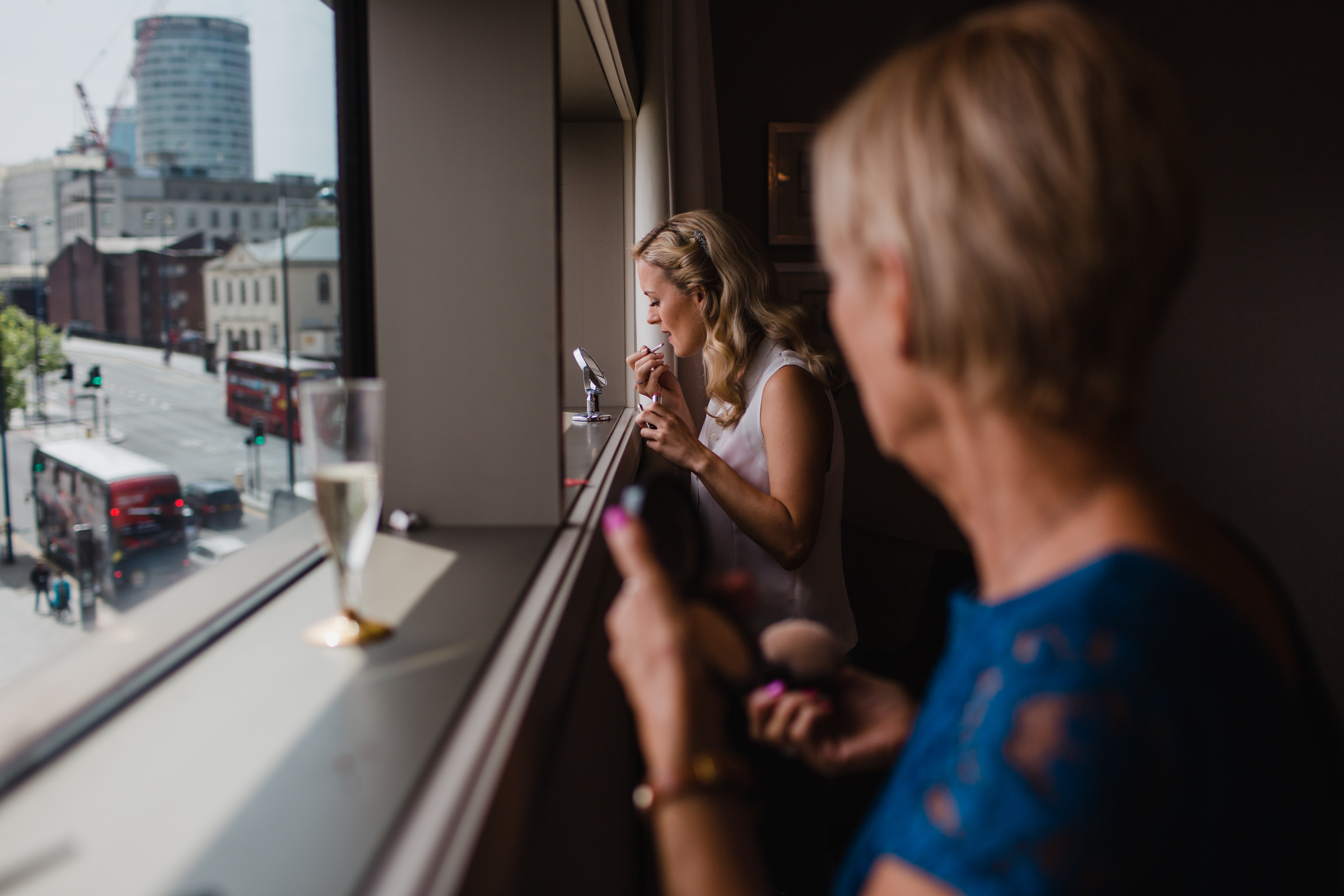 a bride puts het make up on while her mother watches before her Birmingham wedding.