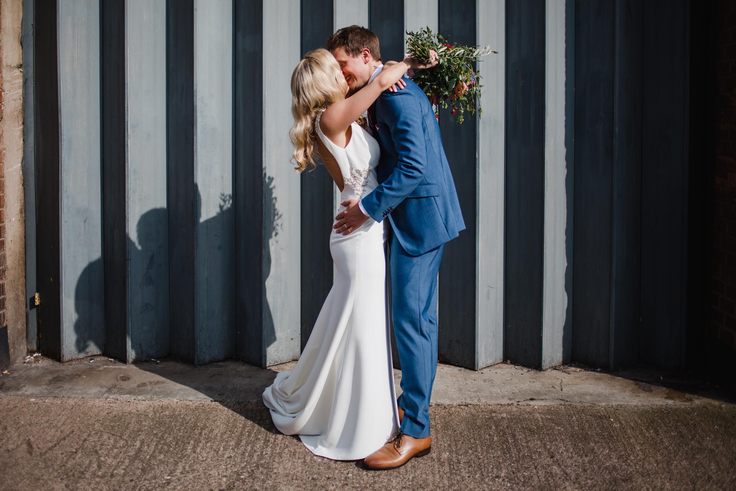 a bride and groom kiss in front of an industrial shutter door in digbeth Birmingham