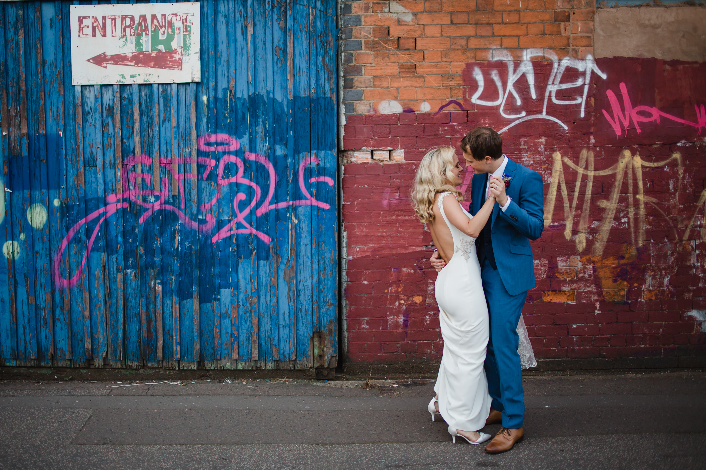 a bride and groom dance in front of graffiti ion their wedding day in digbeth Birmingham