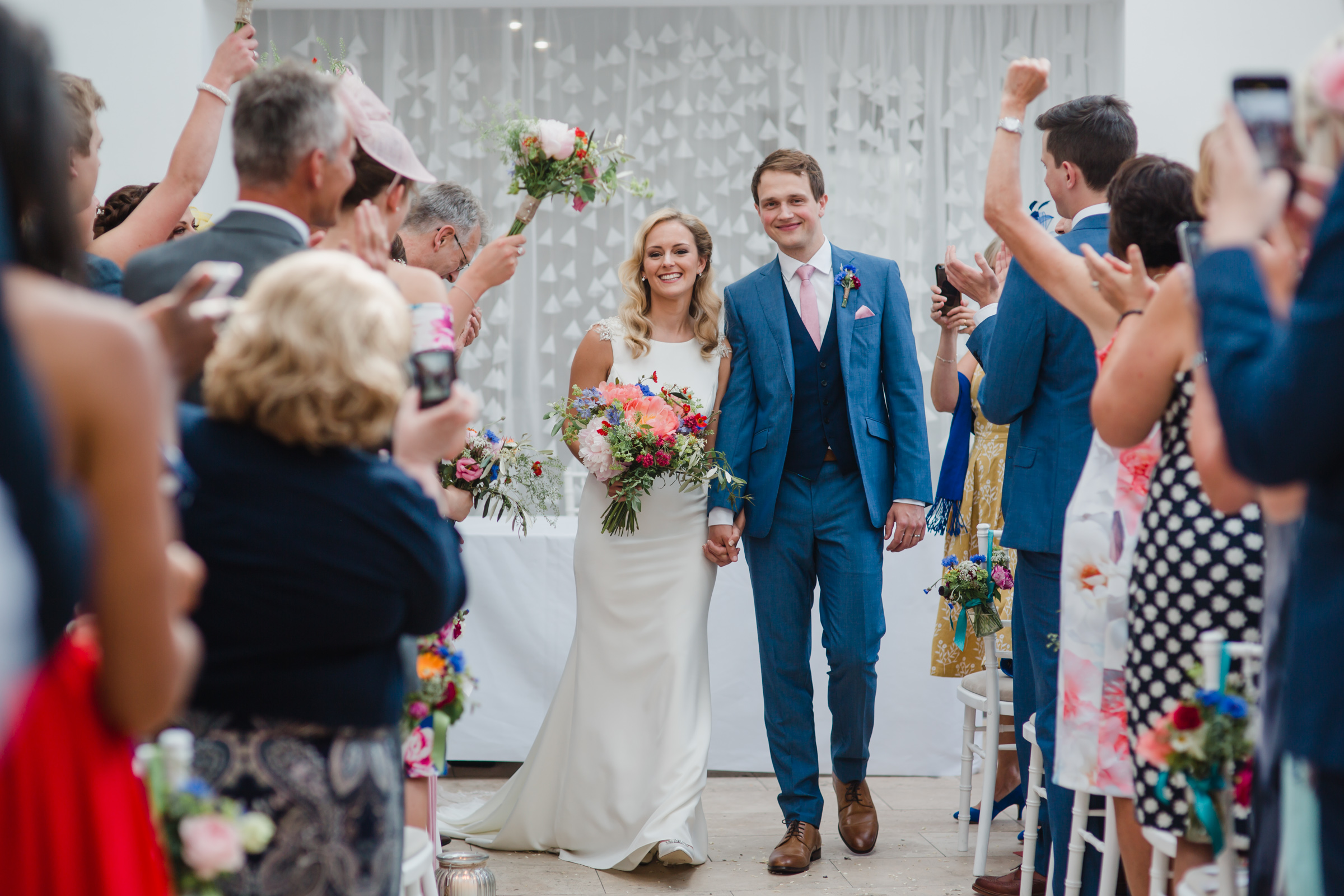 the bride and groom exit down the aisle after their wedding at fazeley studios birmimgham