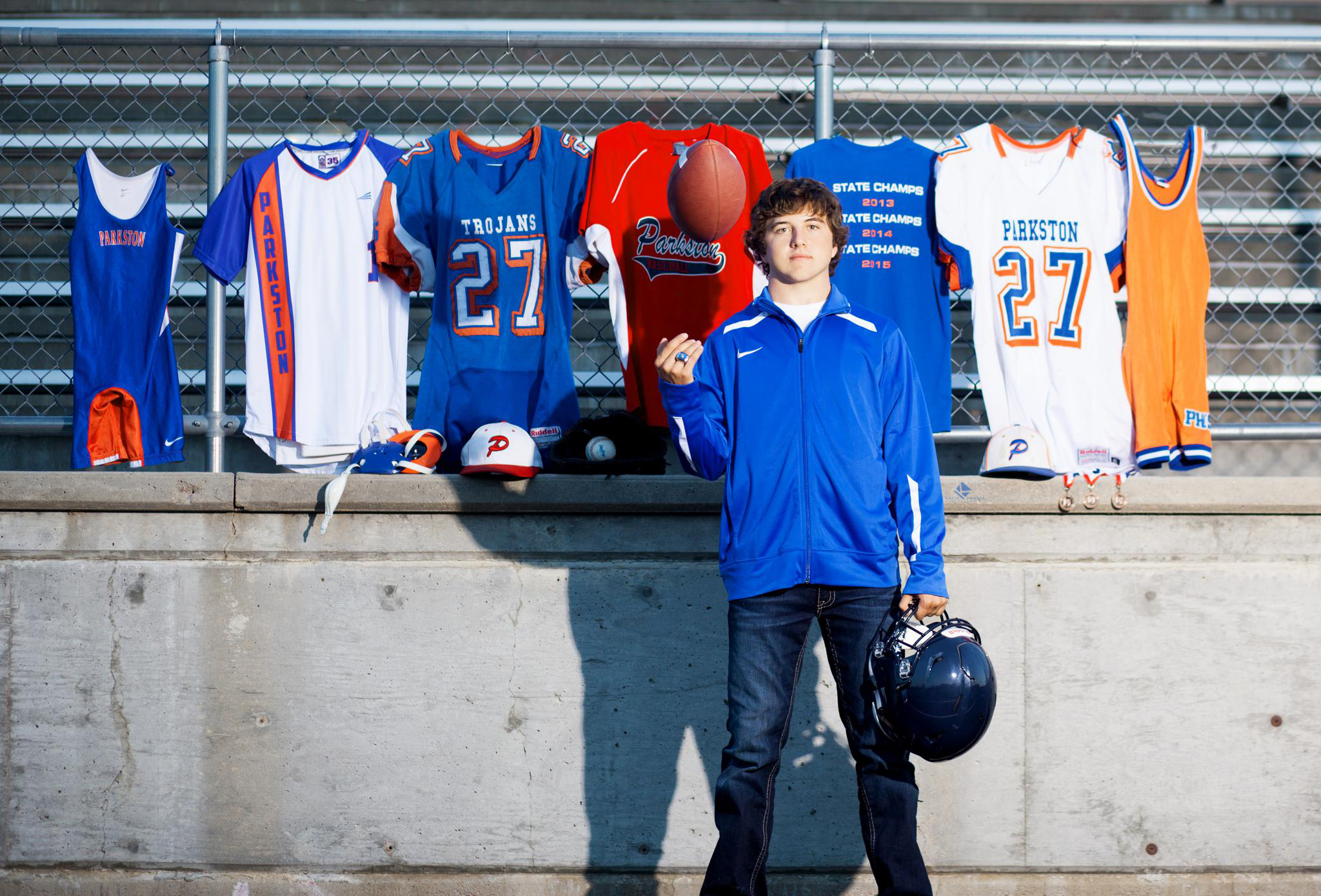 brunette senior guy standing in front of high school jerseys tossing a football in the air