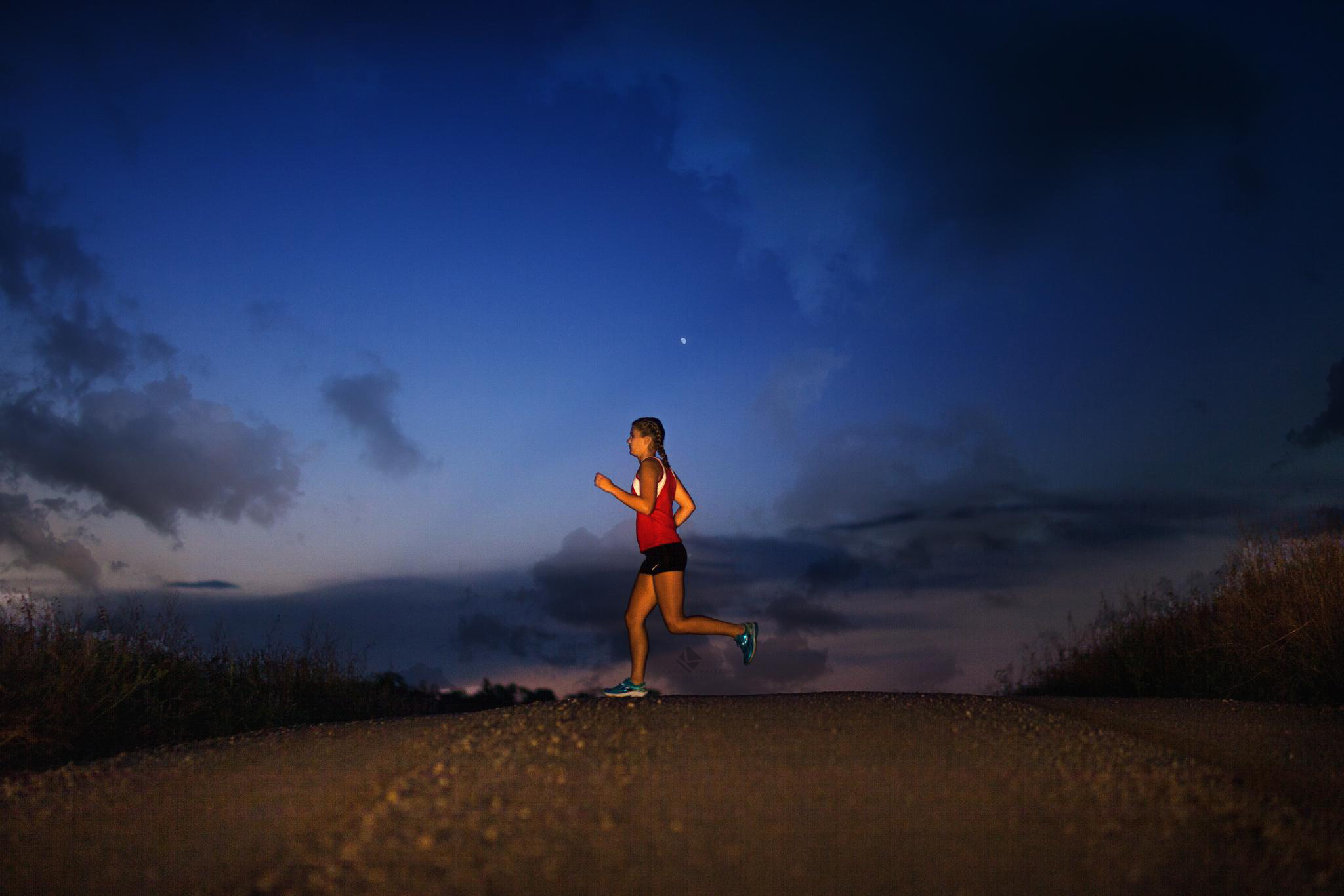 blonde senior girl running at night on a gravel road in a cross country uniform