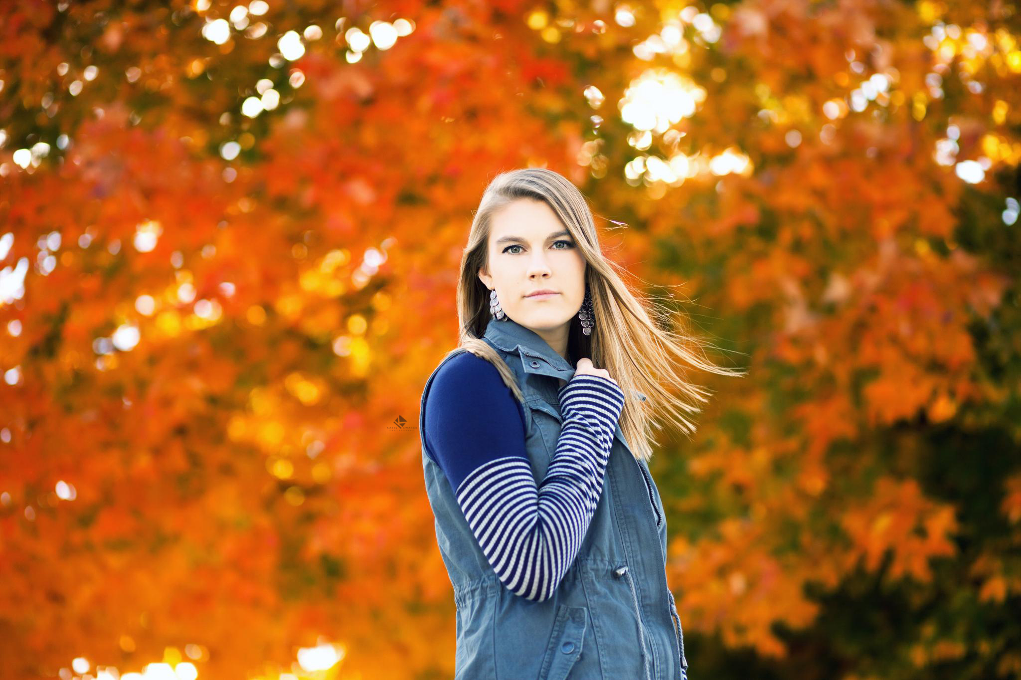 blonde senior girl in a blue striped shirt and blue vest standing in front of fall foliage
