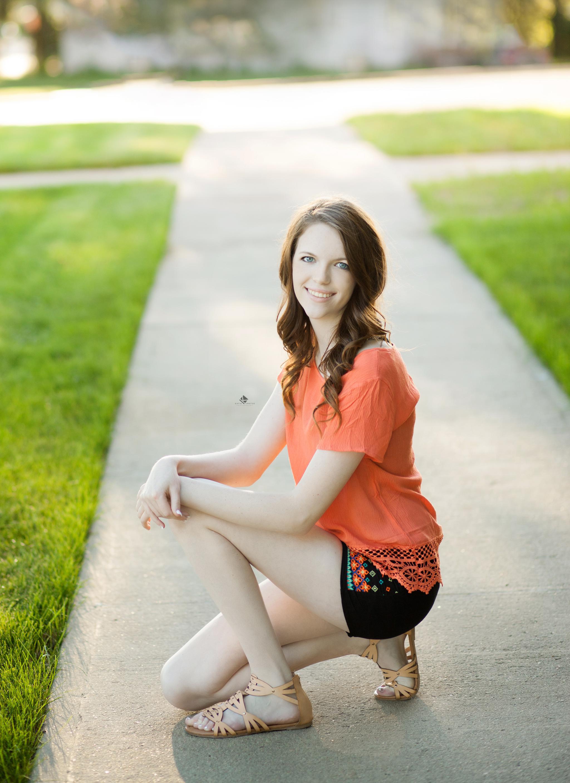 red headed senior girl in a coral top kneeling down on a sidewalk