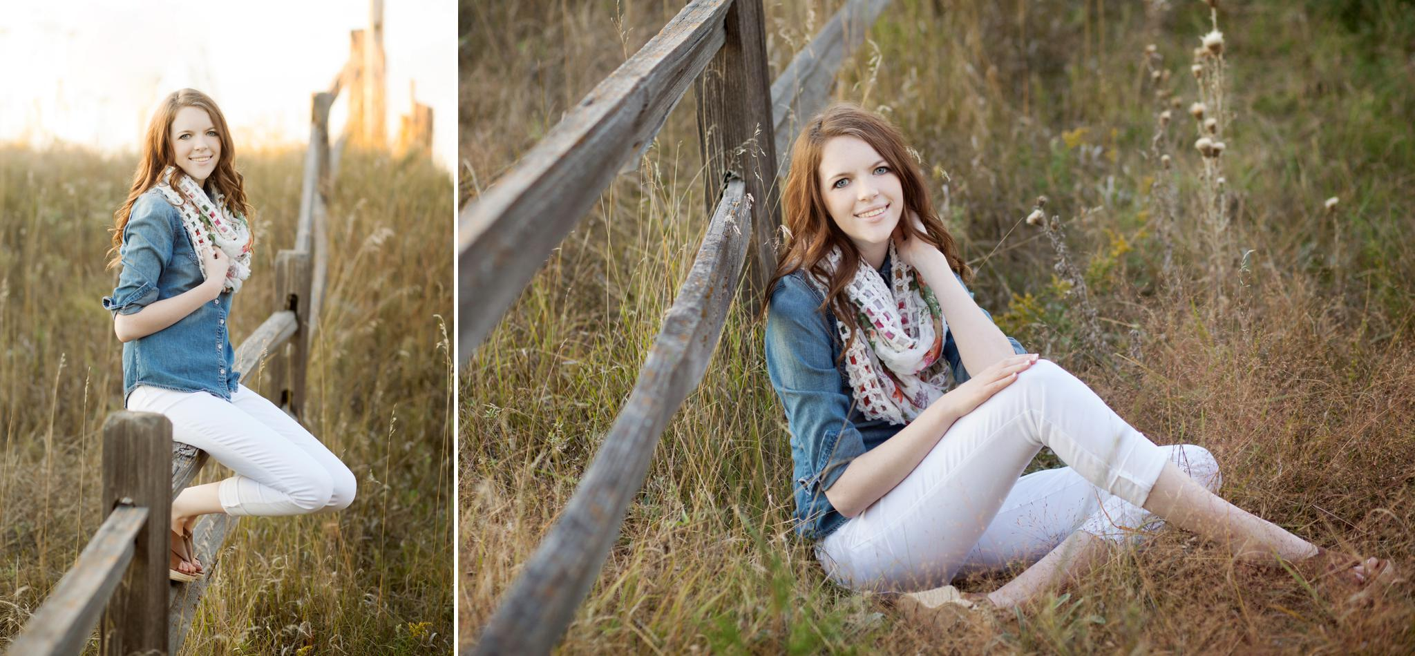 red headed senior girl in a denim top and white jeans sitting next to and on an old fence in the country