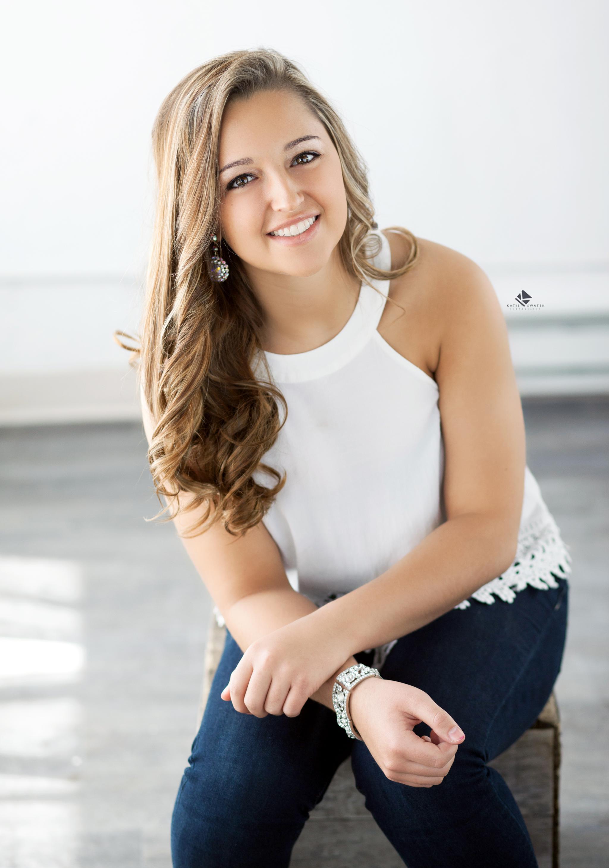 brunette senior girl in a white top and dark denim jeans in a white studio setting