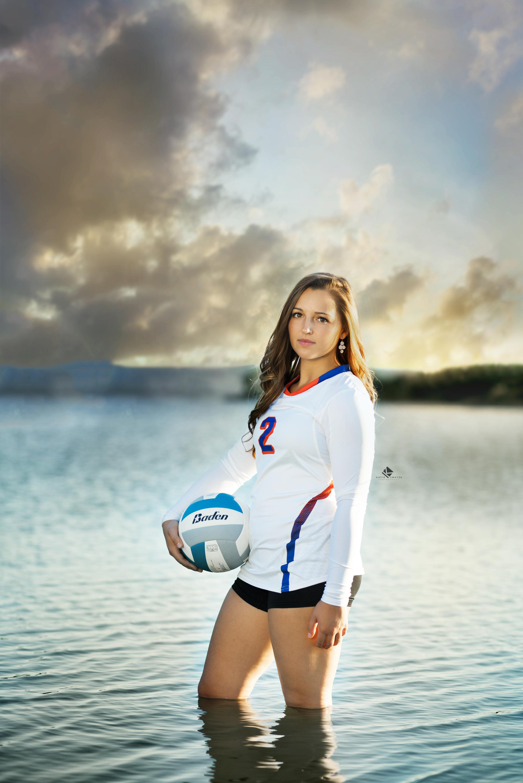 brunette senior girl standing in the lake wearing her volleyball jersey and holding a volleyball