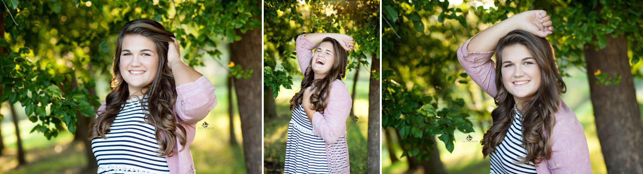 brunette senior girl in a pink jacket over a white and black striped top stands next to bright green trees with natural backlight