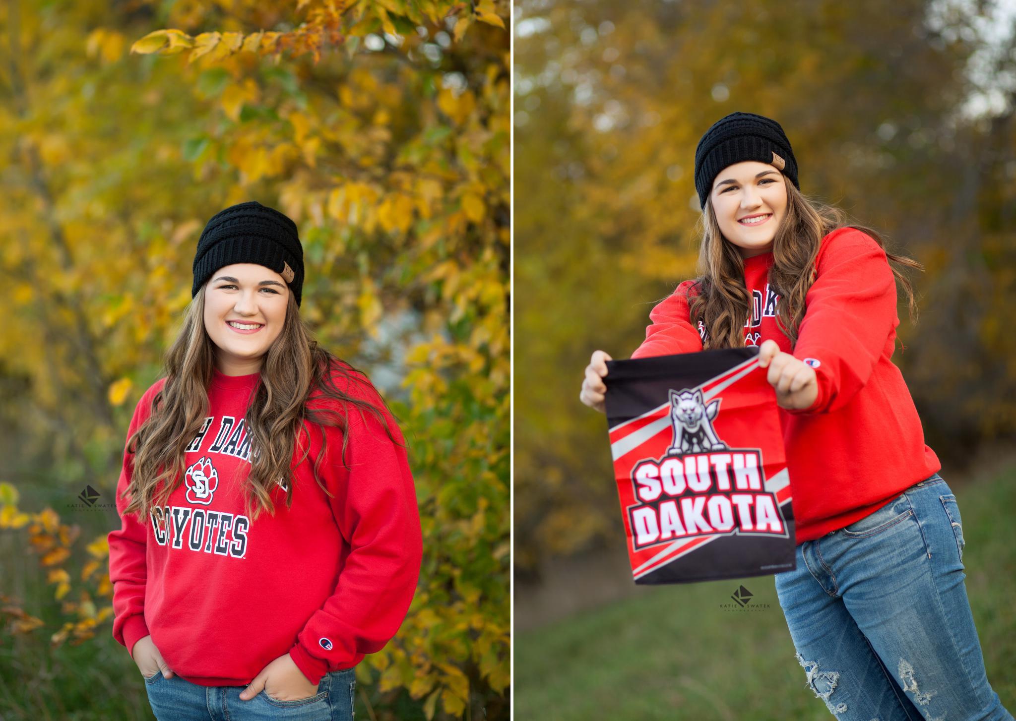 brunette senior girl in a black stocking cap wearing a University of south Dakota sweatshirt posing for senior pictures in the fall colors