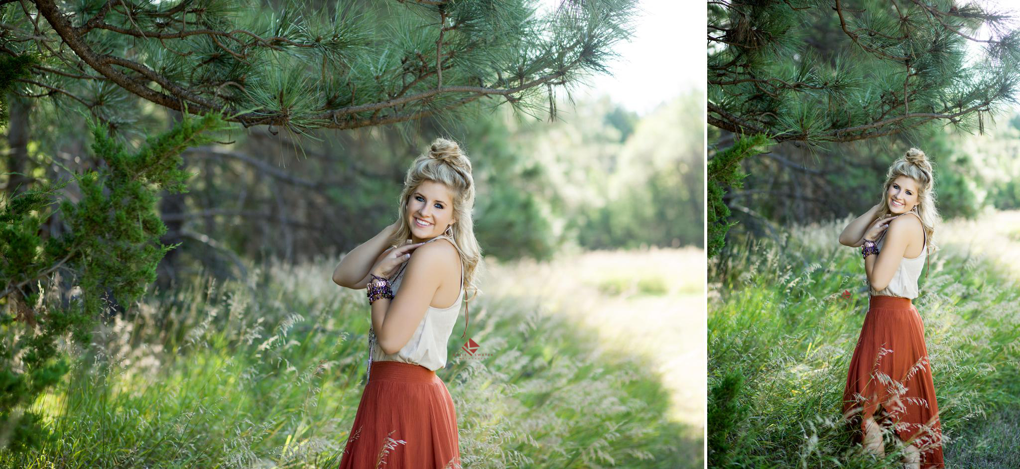 blonde senior girl in an ivory top and a rust colored skirt standing near evergreen trees