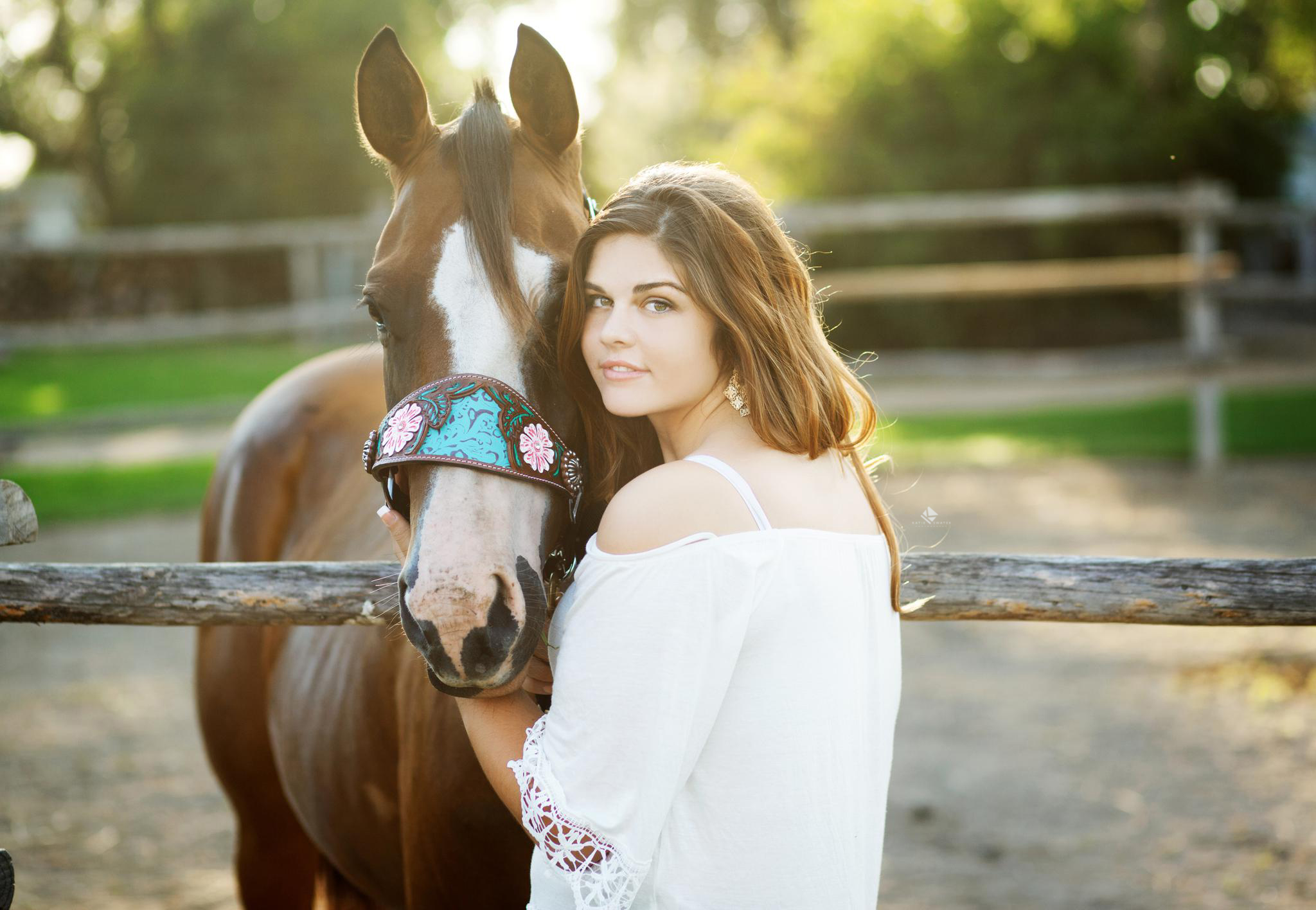 brunette senior girl in a white lace top posing with her horse at a fenceline