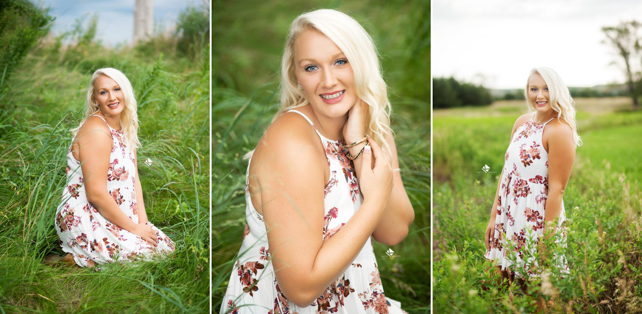 blonde senior girl in a white and red floral dress standing in in a field of very green grass