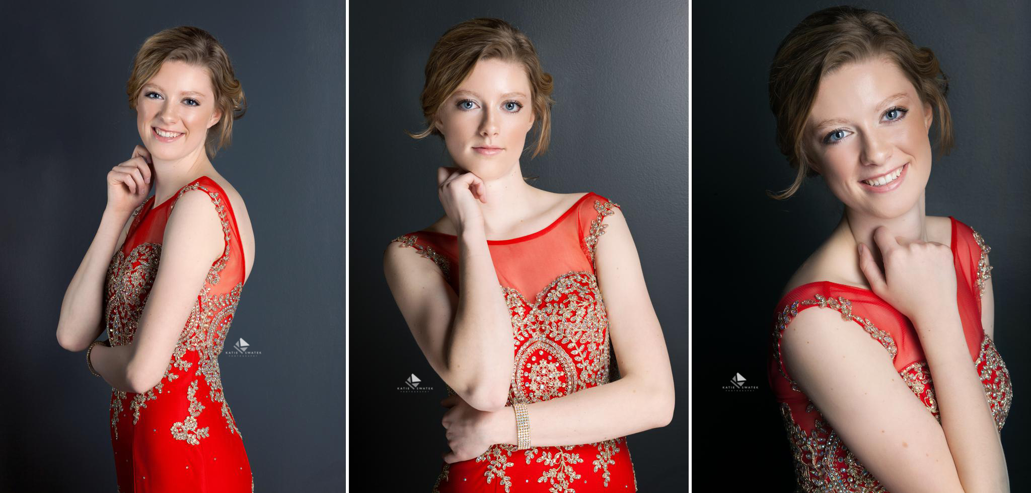 blonde senior girl in a red prom dress standing against a dark blue background in a studio set up