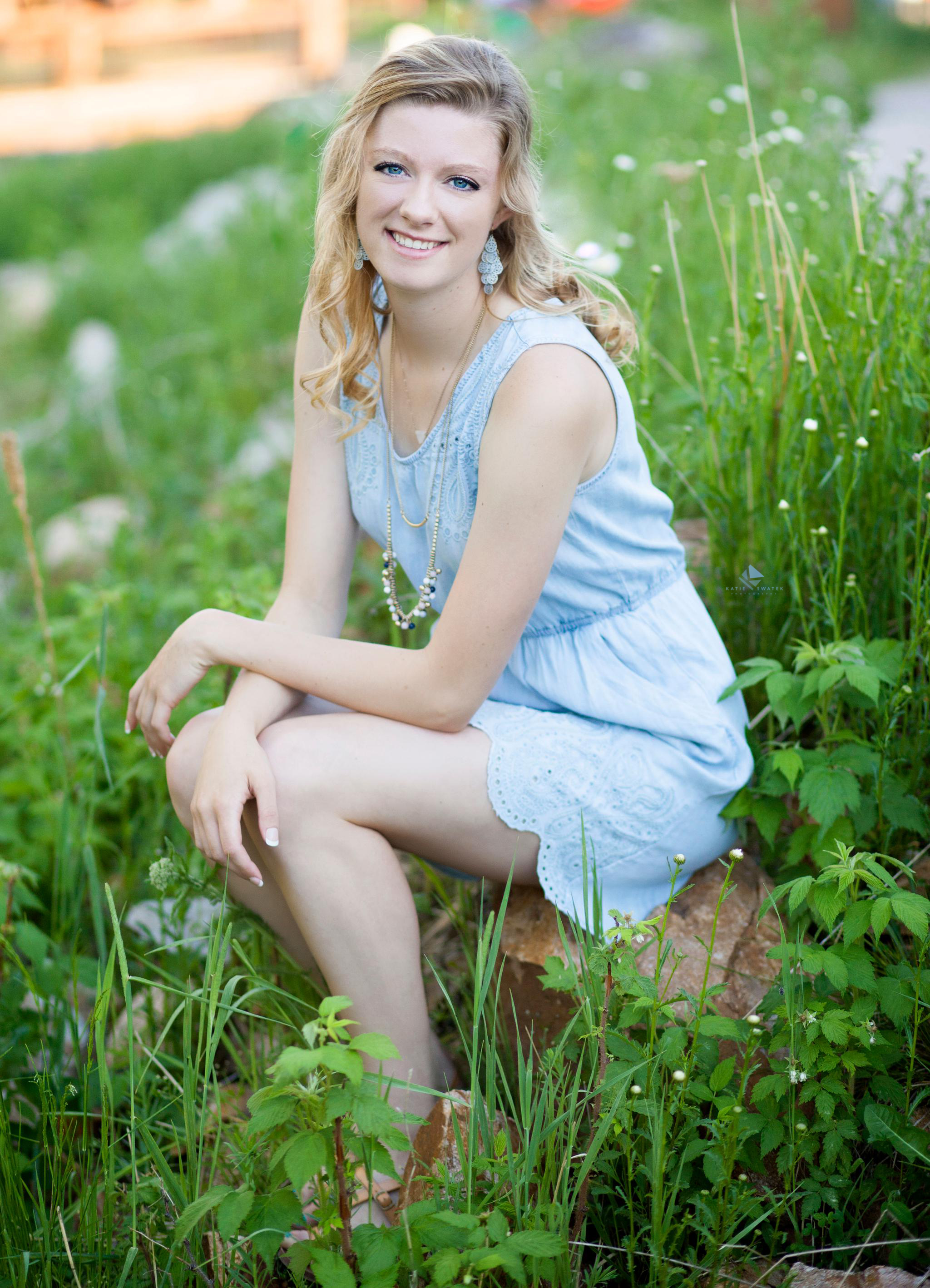 blonde senior girl in a denim dress sitting in the Black Hills National Forest in Deadwood SD