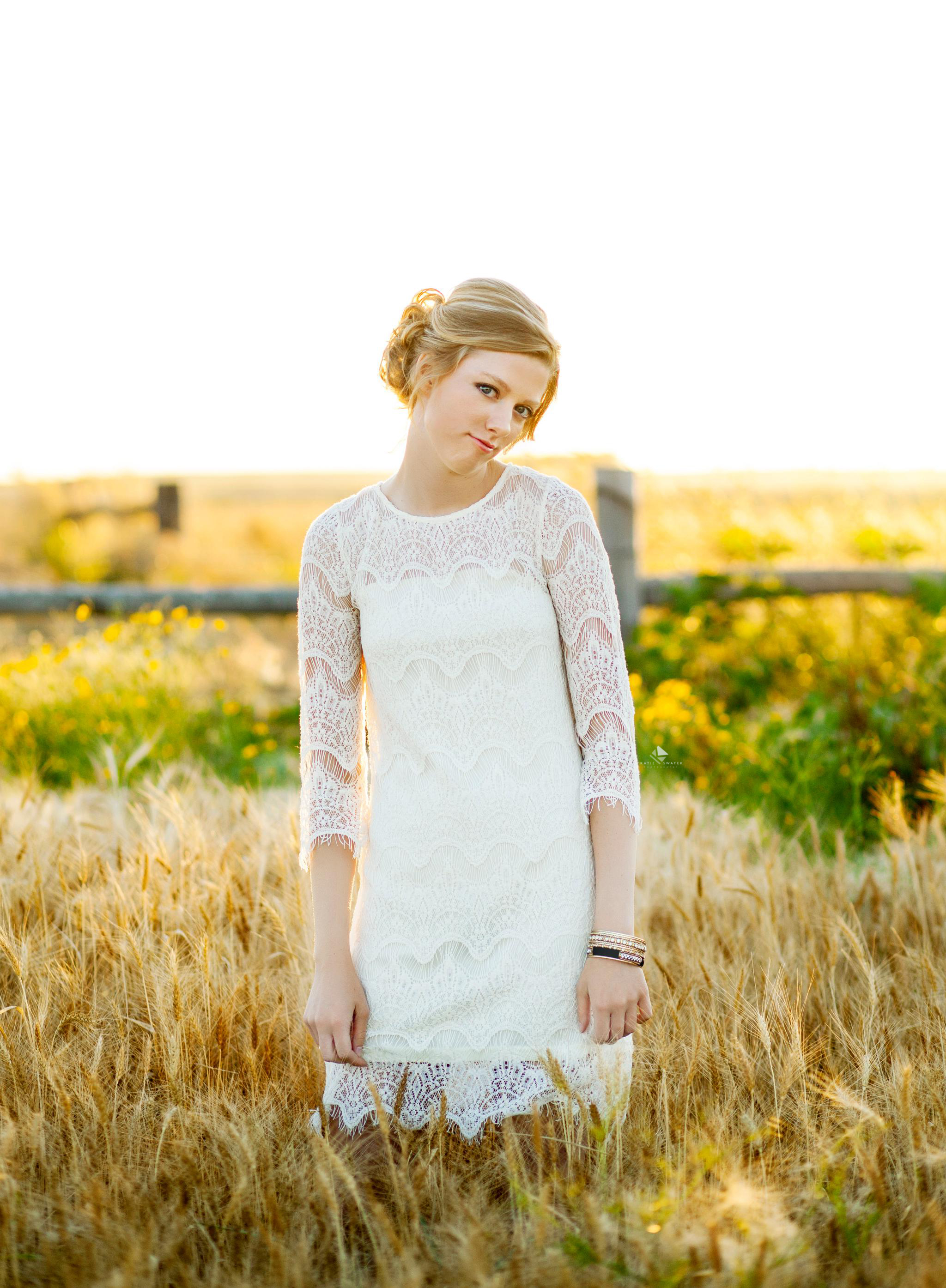 blonde senior girl in a white dress posing in a white and flower field for senior pictures