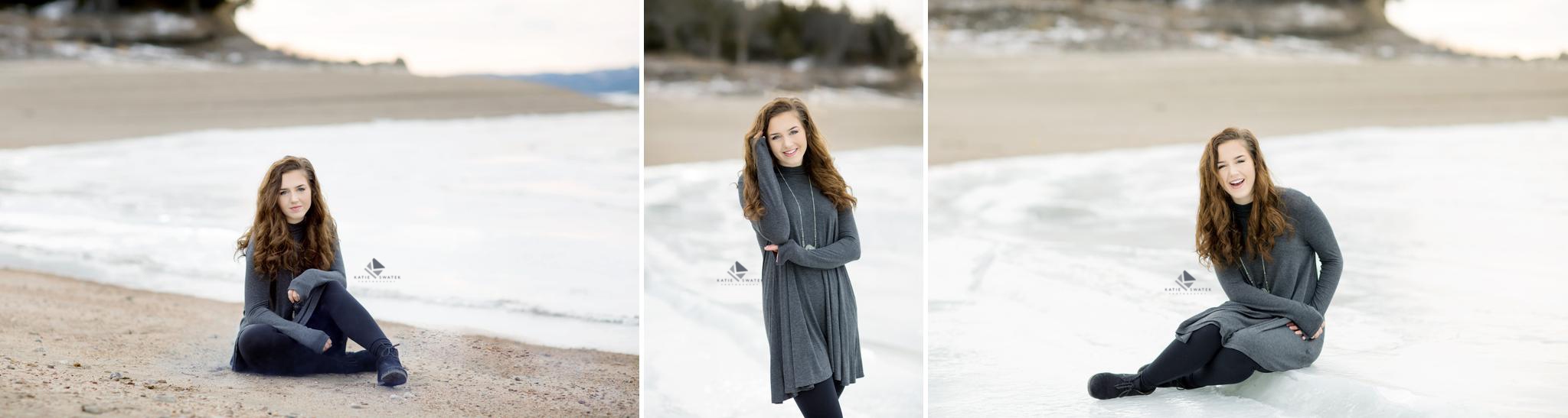 brunette senior girl in a gray sweater dress and black boots sitting on a frozen beach in January in South Dakota