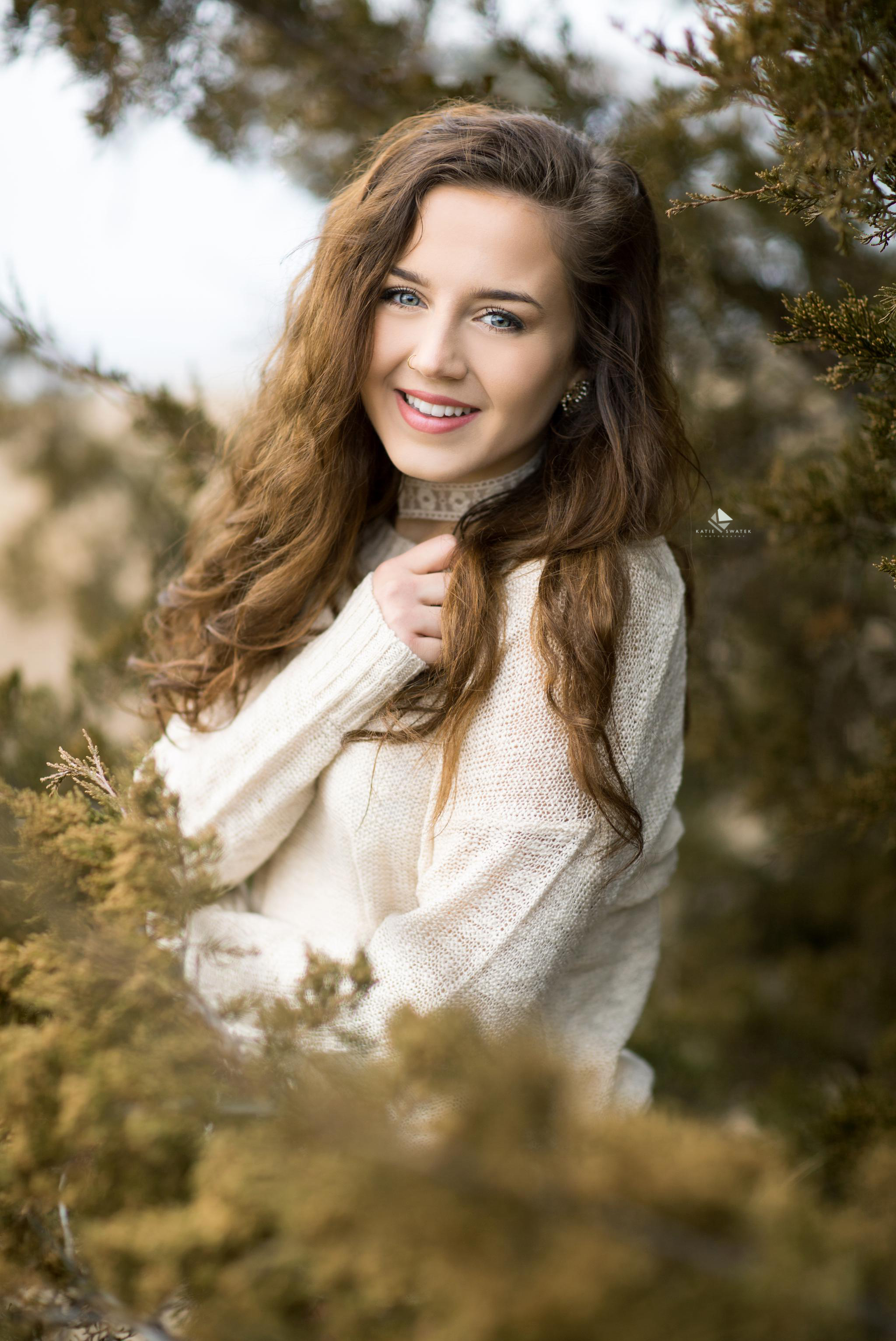 brunette senior girl in a cream colored sweater standing in an evergreen tree