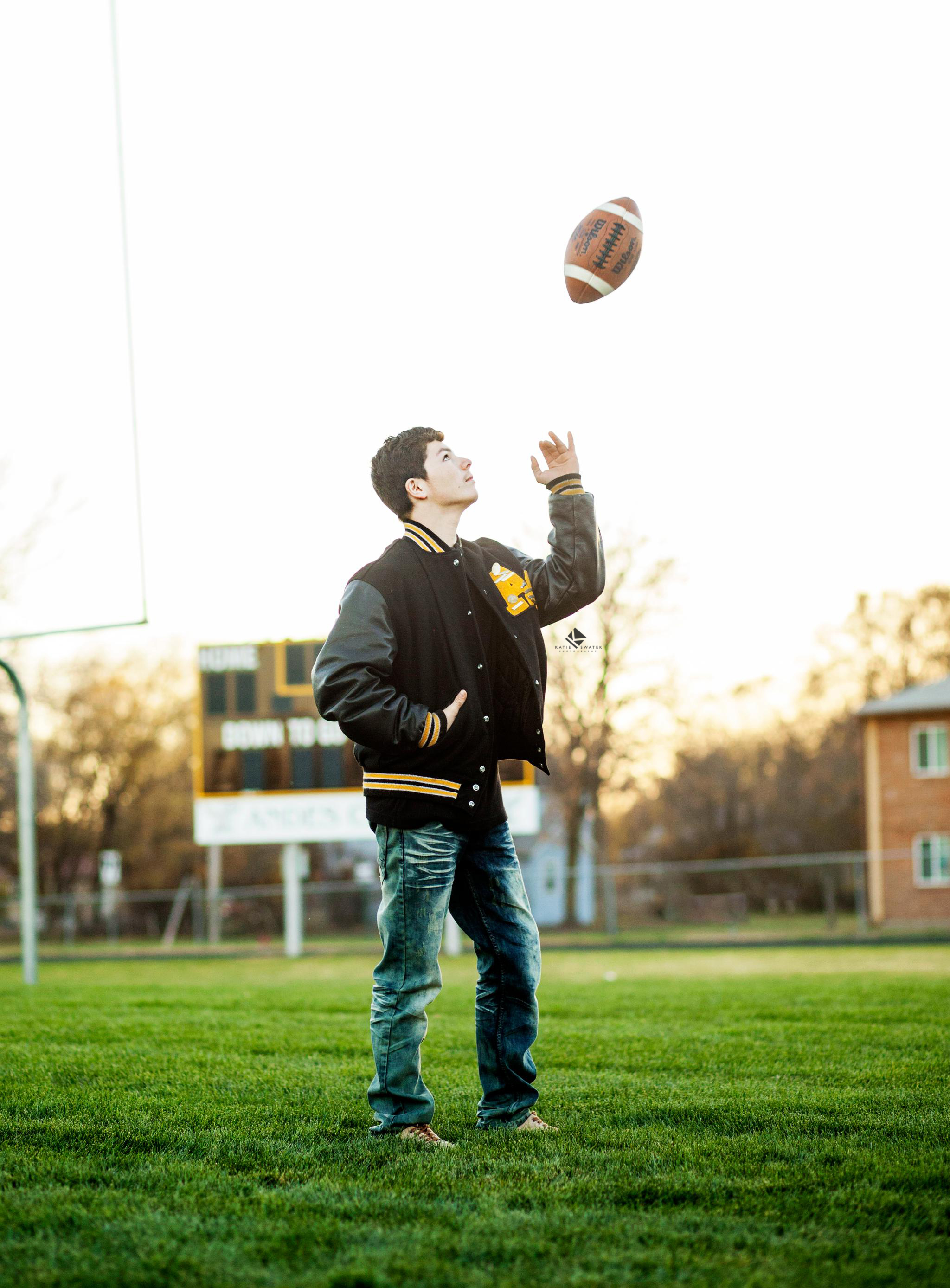 black haired senior guy in a letterman jacket standing on a football field tossing a football in the air