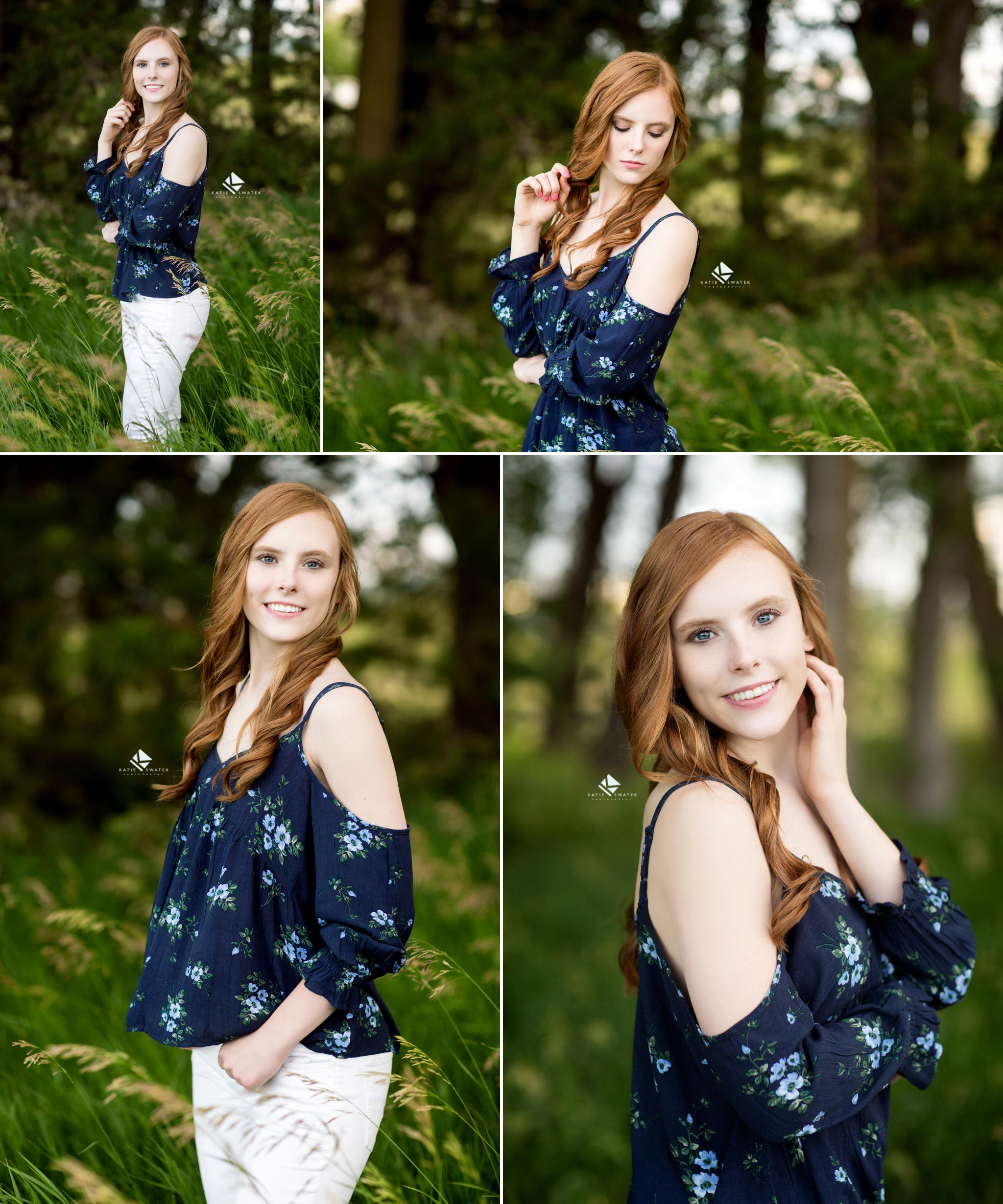 Red headed senior in a navy blue floral top and white pants standing in a grassy, tree covered area for senior pictures