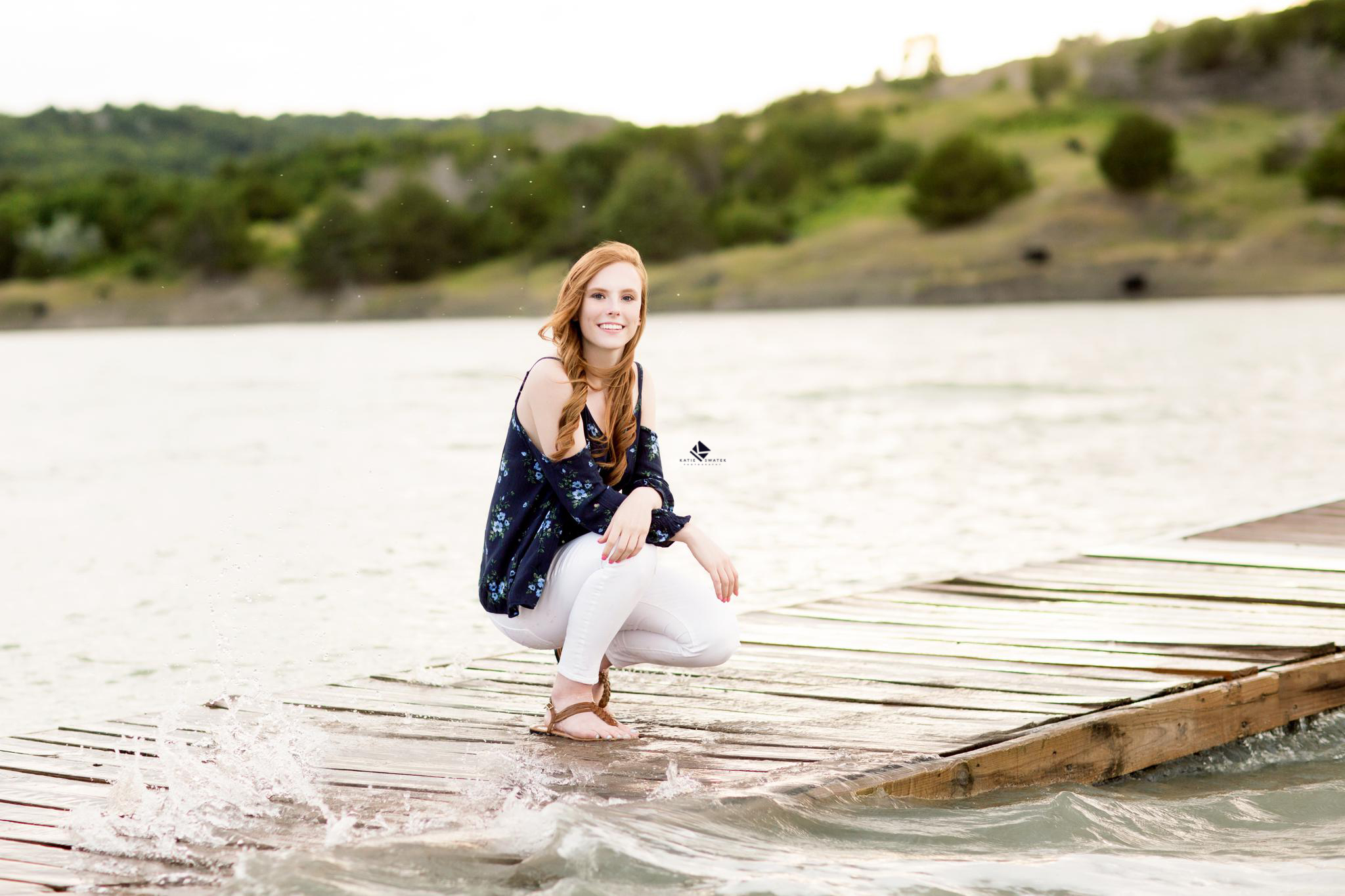 Red headed senior in a navy blue floral top and white pants squatting on a dock surrounded by waves and water with a green hill in the background on Lake Francis Case in South Dakota