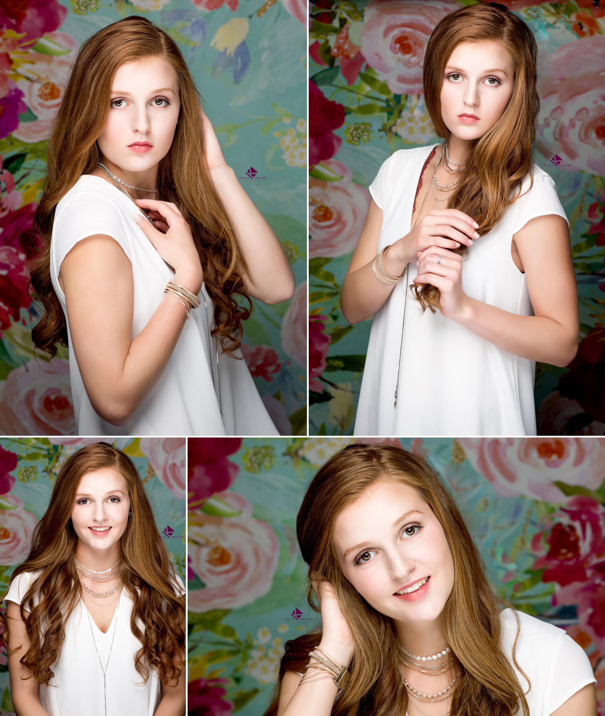 red headed senior in a white dress with a thin silver necklace standing in front of a pink and green floral background in the studio