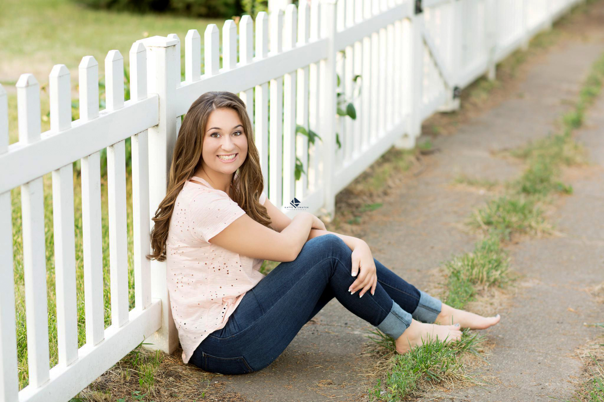 barefoot, brunette senior girl in a pink top and dark denim jeans posing next to a white picket fence