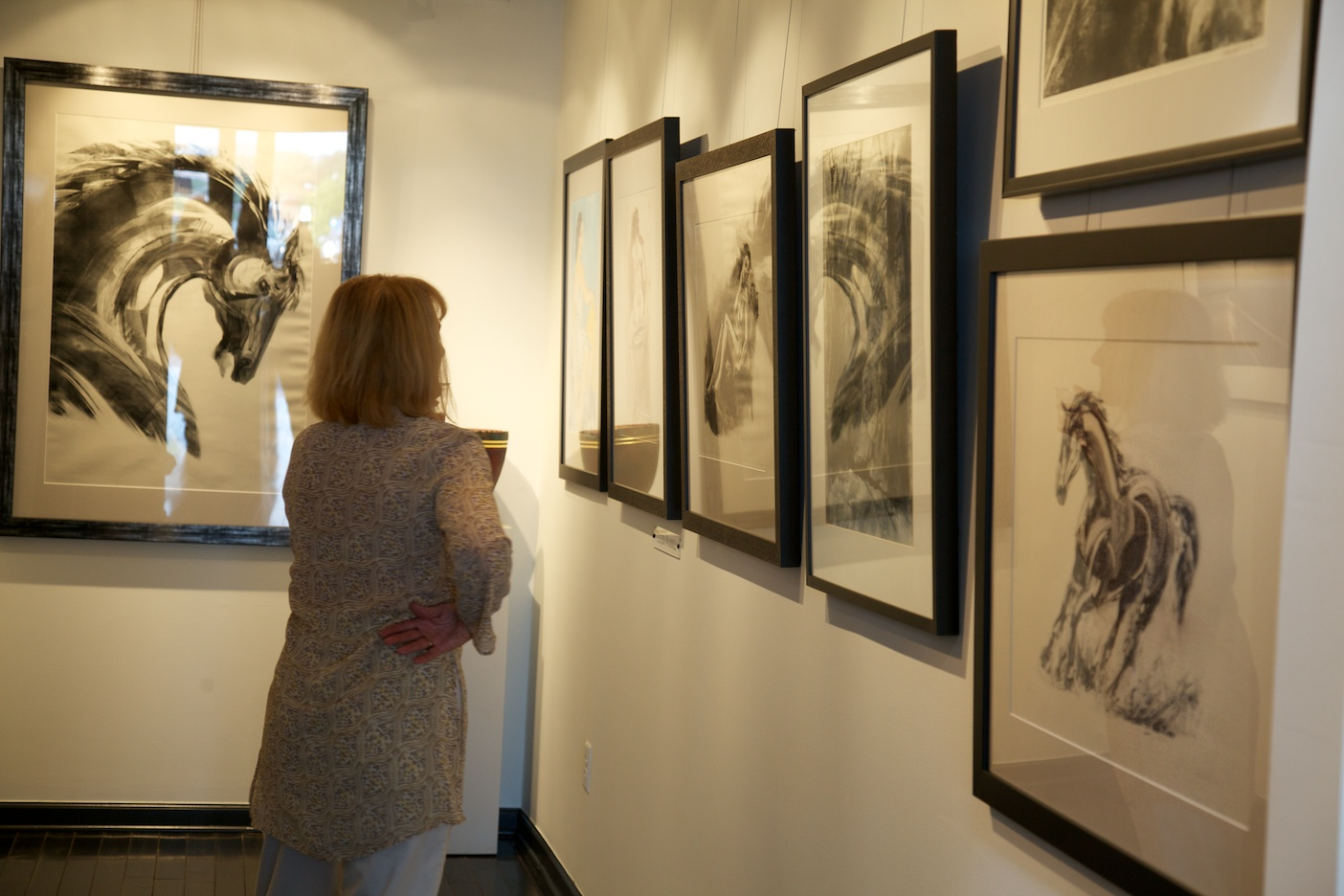 """Victoria Schomer of ASID and Green Built Environments admires some of Alyson Markell's monoprints    Back wall: """"Equus""""  Bottom right: """"Running Horse"""""""