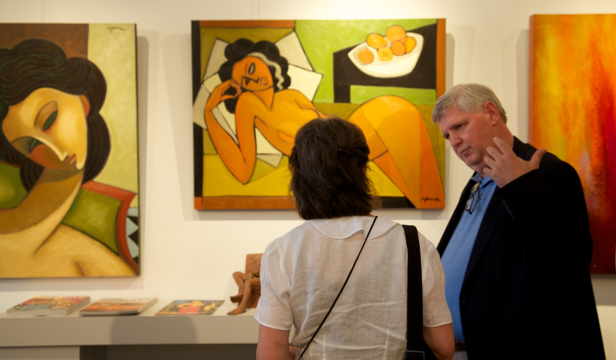 """Gallery director, Perry Magee, shares details about the artists to an ASID member     Left: """"Girl with Green Eyes"""" by Marsha Hammel    Center: """"Naranjas"""" by Marsha Hammel"""