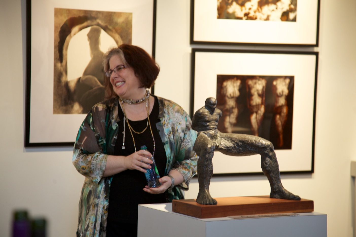 """Artist, Amy Medford with her sculpture, """"Metamorphosis""""    Left: """"Torso Climbing Out"""" by Robert Asman   Right: """"Three Scratched Figures"""" by Robert Asman"""