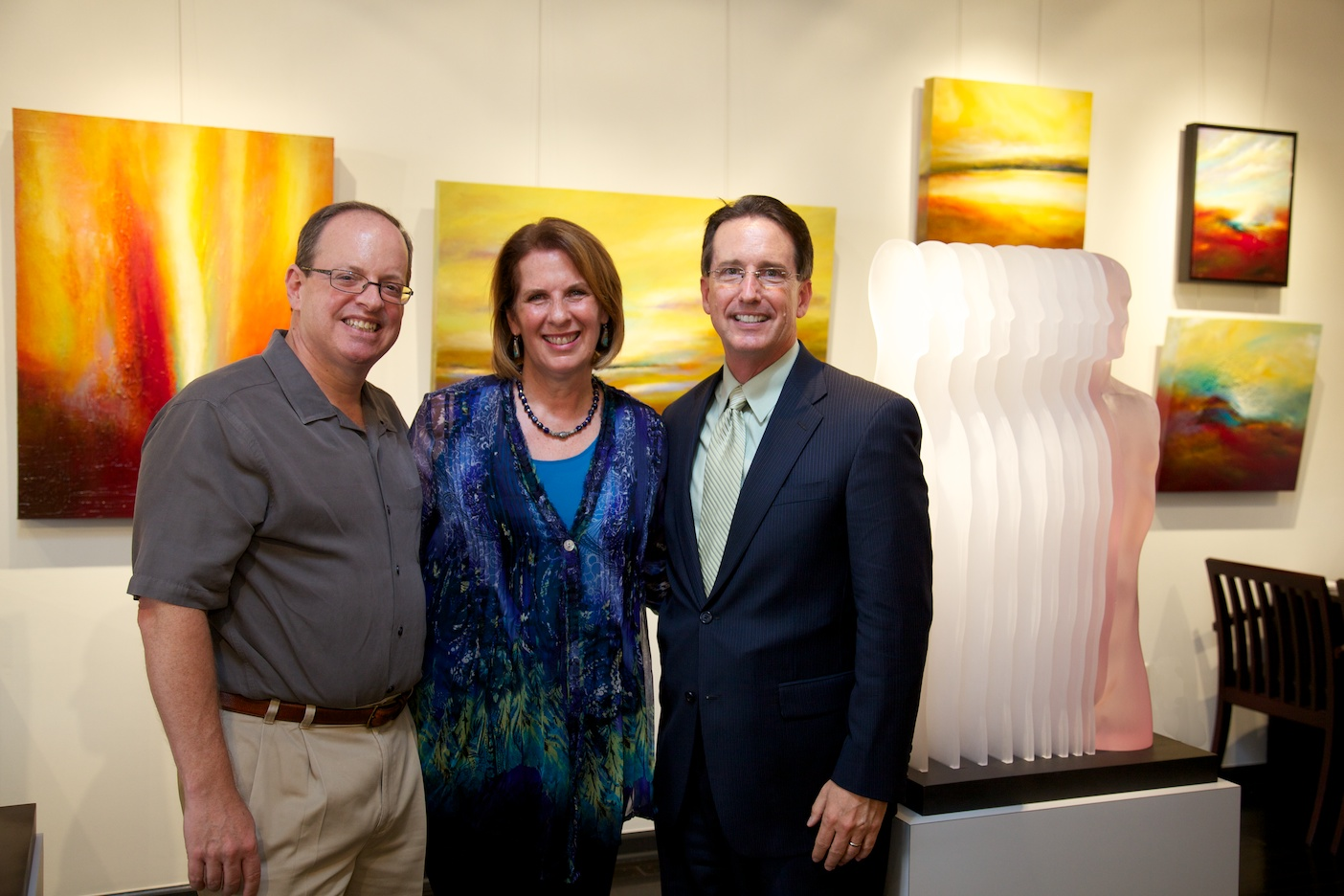 """Gallery chairman, Russell Medford, gallery president, Margaret Offermann, and Director of Philanthropic Initiatives at Mission Foundation, John Locke    Sculpture: """"Fade Away"""" by Leonid Siveriver   Left: """"Living for a Dream"""" by Michael Ethridge"""