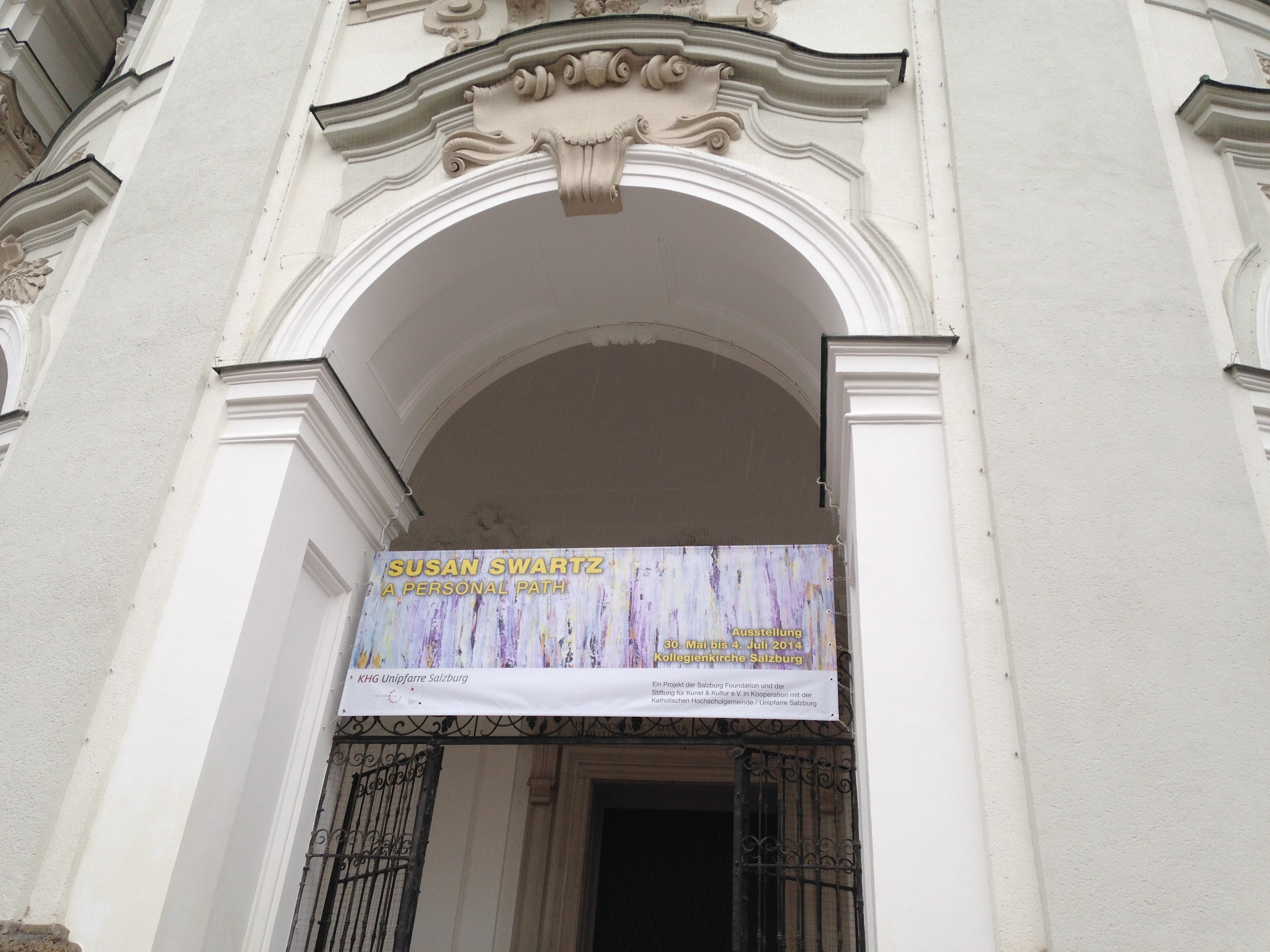 A banner hangs at the front entrance of the Kollegienkirche in Salzburg, drawing visitors into the exhibition within.