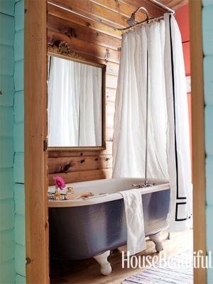Knotty pine plank paneling in bathroom with clawfoot tub |Designers: Studio Due, Image via:   House Beautiful