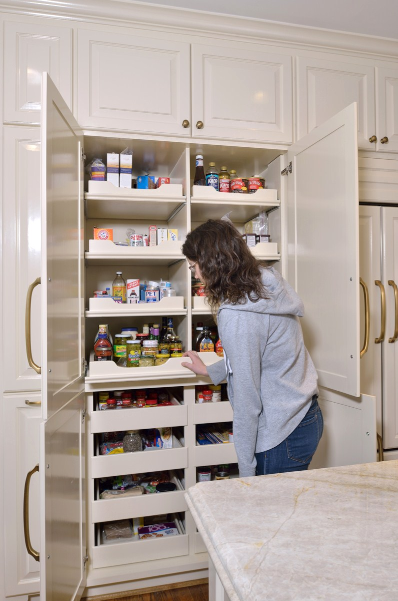 The pantry:Previously located in a small closet, it was redesigned as a custom wall of cabinetry with better access and more storage. While we were at it, we hid that trash too.