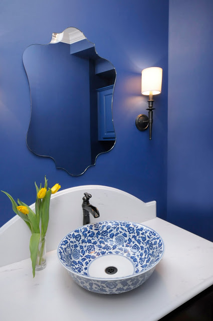 Sconces work well with the shapely mirror in this blue bathroom. Carla Aston, Designer #bathlight #vanitylight #wallsconce