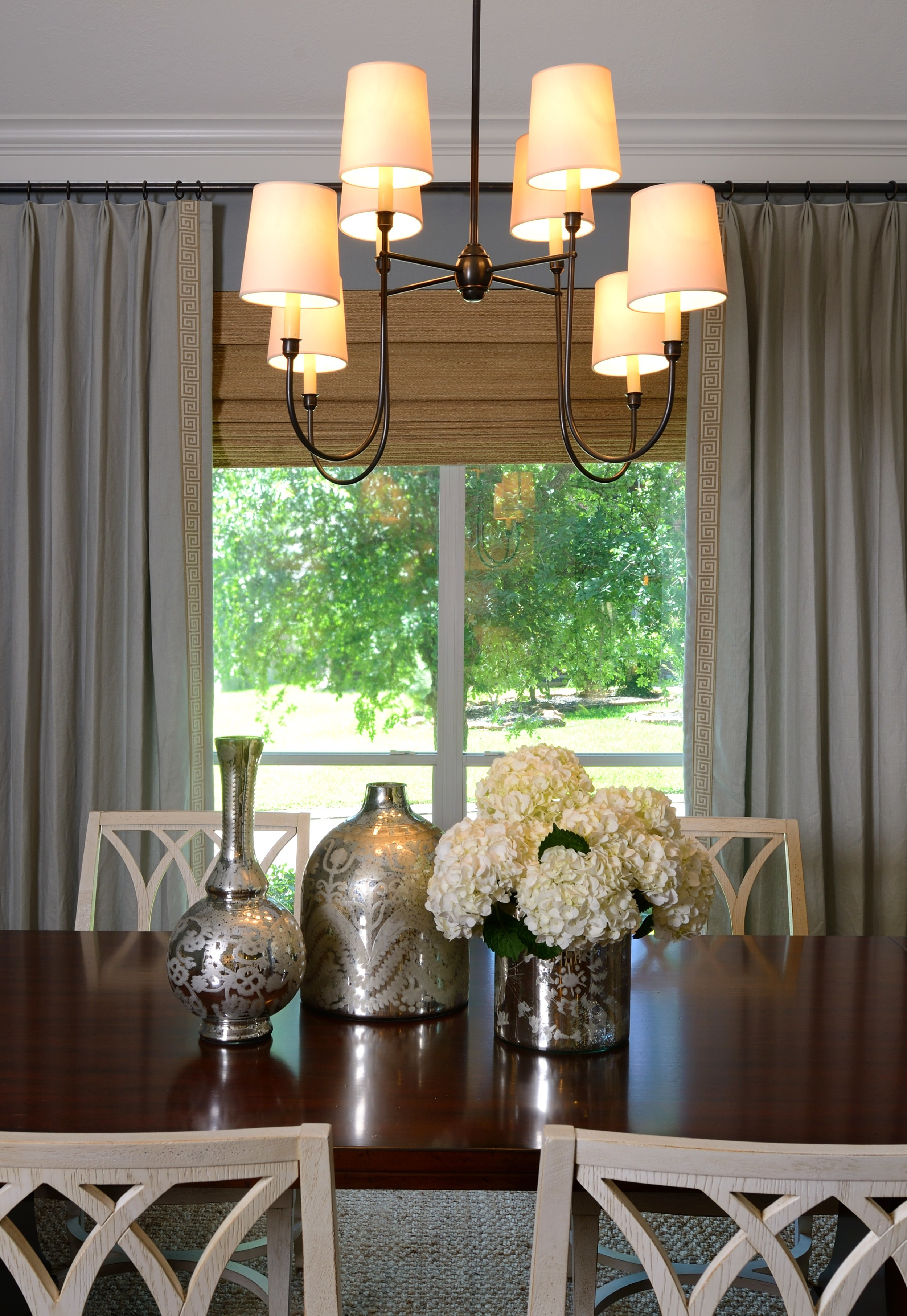 Dining room with custom window treatment and white chairs, Designer: Carla Aston