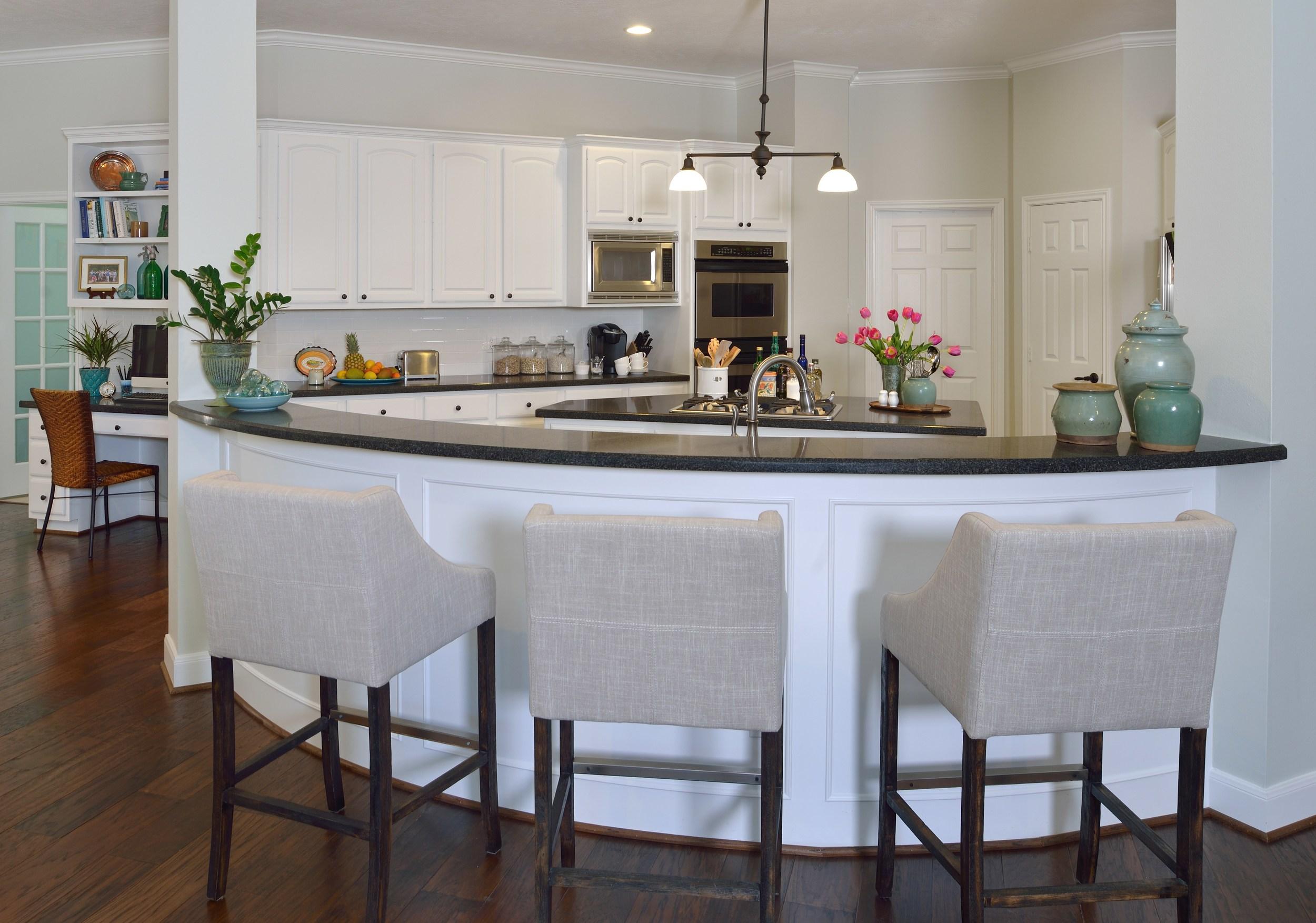 White kitchen with linen covered barstools, Designer: Carla Aston