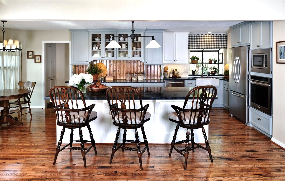Before & After: A cottage / country style kitchen enjoys wide open space | Interior Designer: Carla Aston / Photographer: Miro Dvorscak — soapstone counters, island; white and gray cabinetry; hardwood floor; lighting; hutch