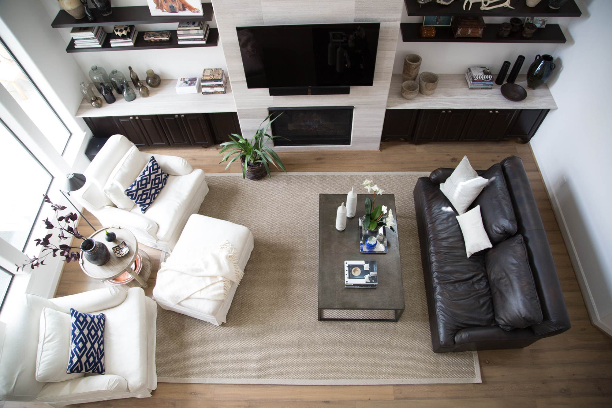 living room remodel; chair; Ottomans; leather sofa; shelving; fireplace; coffee table | Interior Designer: Carla Aston / Photographer: Tori Aston