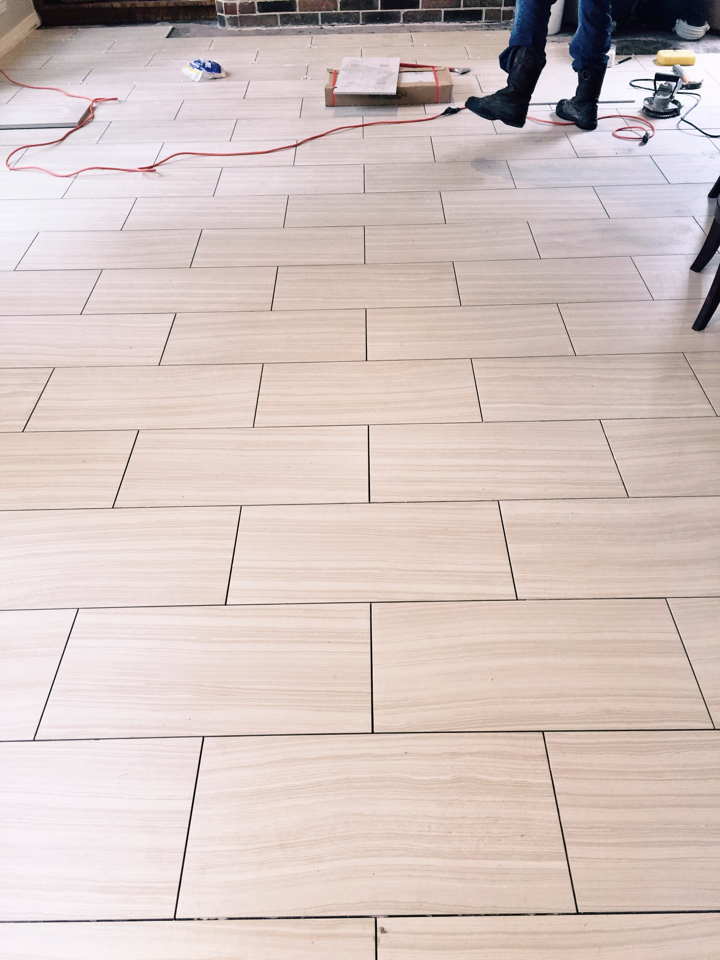 12 x 24 tile floor being laid across the narrow width of the room to make the room appear wider.