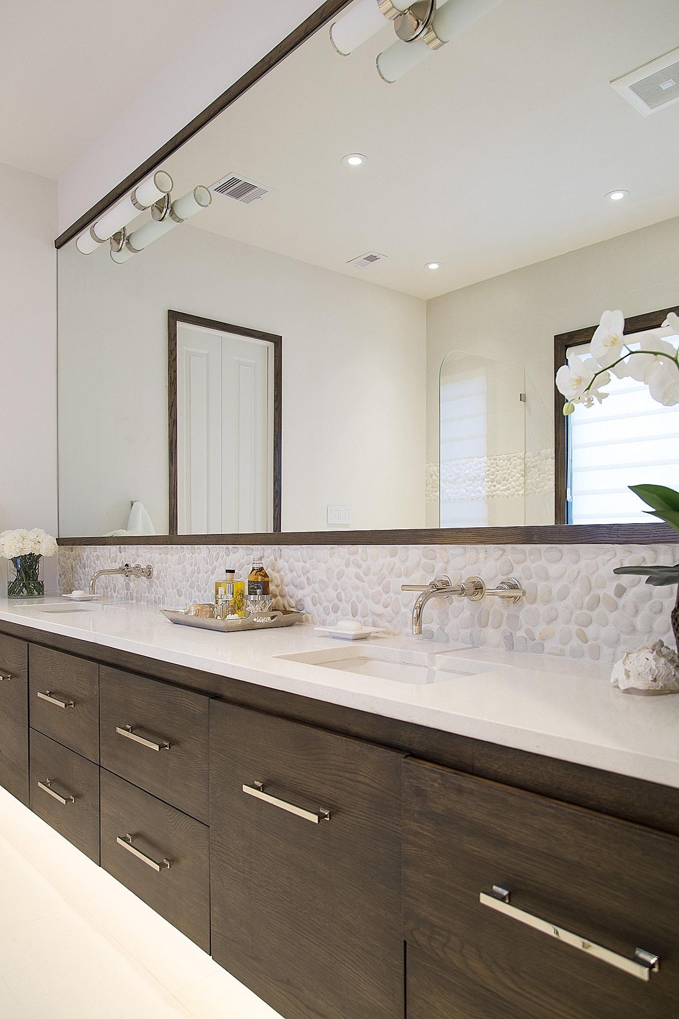 Master bathroom remodel with floating wood vanity and pebble tile backsplash. | Interior Designer: Carla Aston / Photographer: Tori Aston #bathroomideas #bathroomremodel #floatingvanity #bathroomvanity #pebbletile