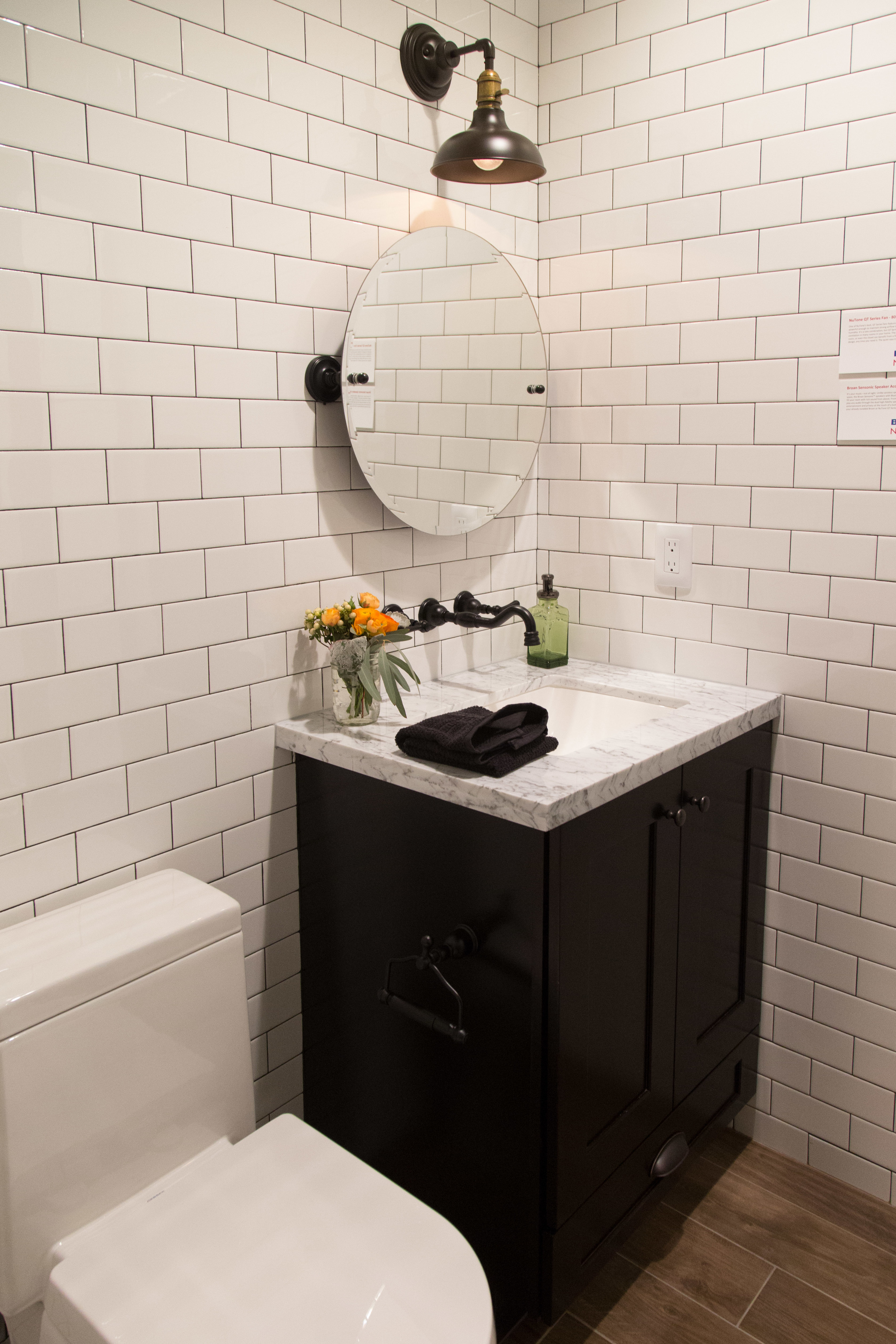 Bathroom in guest suite, subway tile, wall mount faucet, black and white | Interior Designer: Bobby Berk