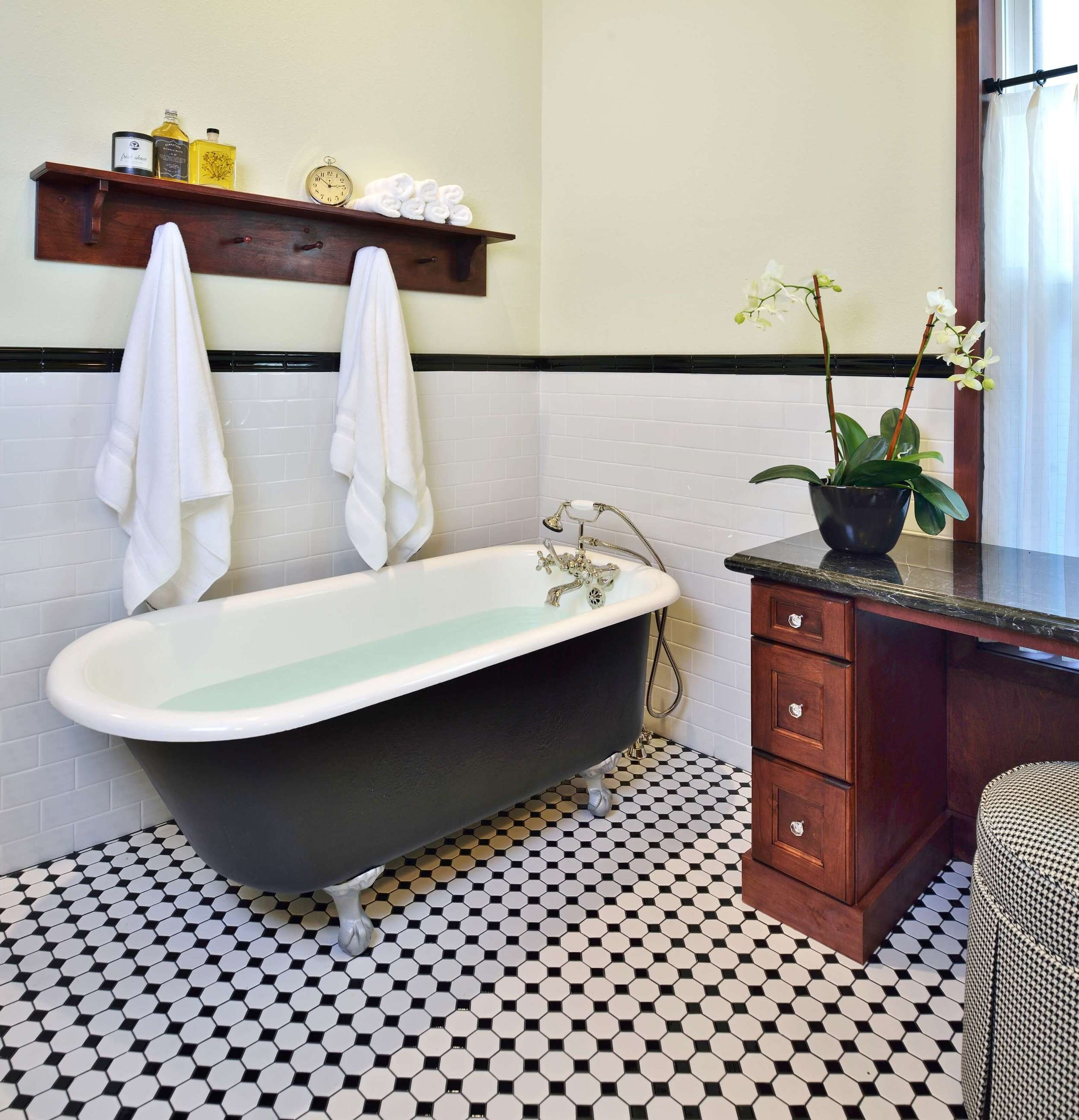 Footed tub in vintage style bathroom remodel with black and white tile floor, Designer: Carla Aston
