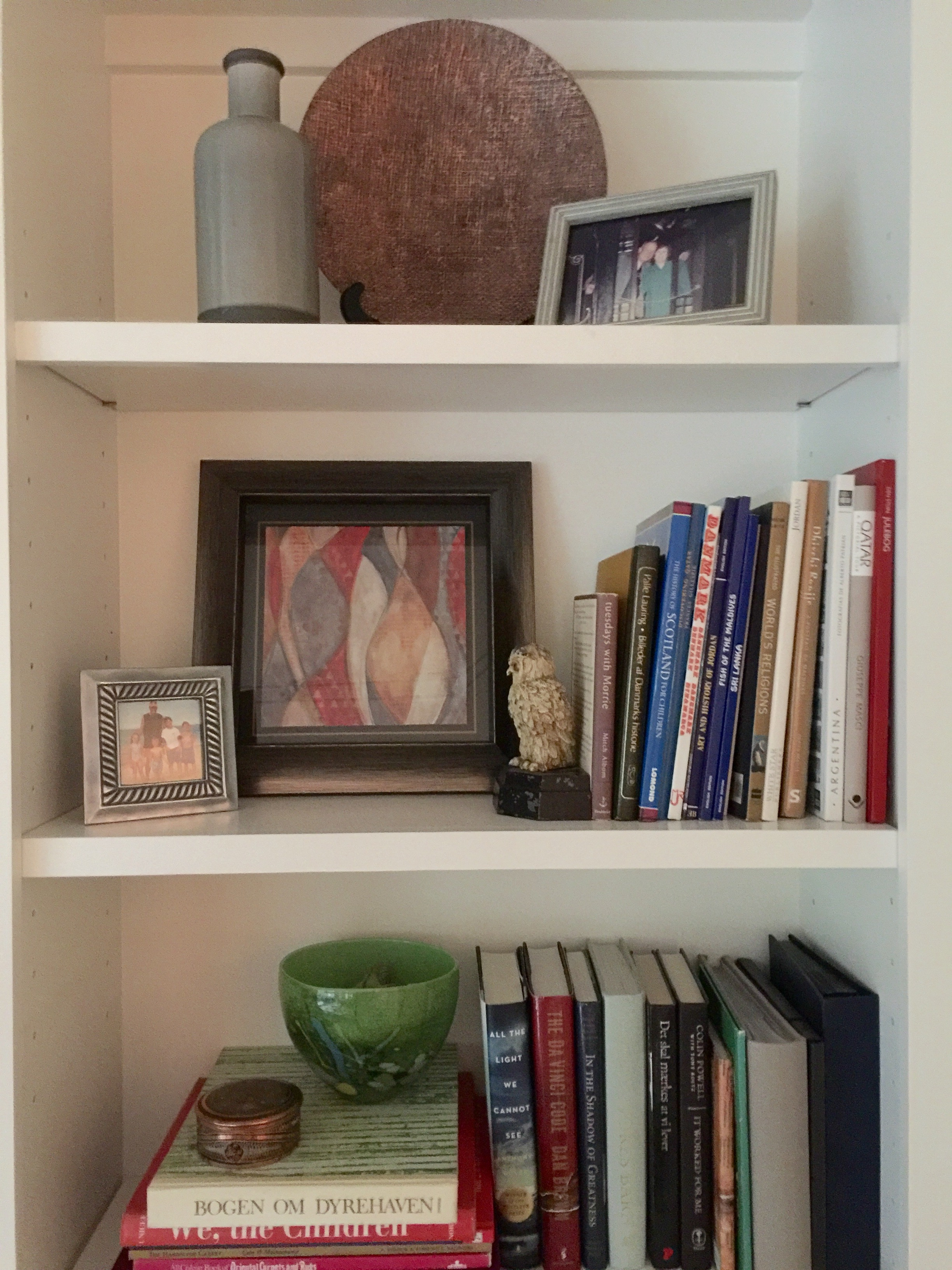 Bookshelf styling - the gray vase, copper toned plate, and modern art piece were from At Home and filled in nicely amongst the homeowner's books and collectibles.