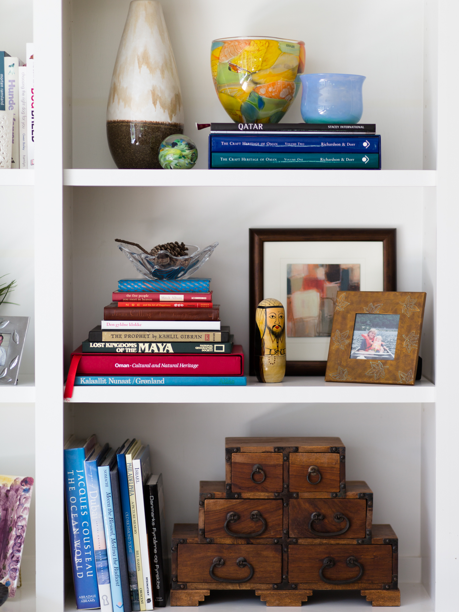Bookshelf Styling - the large two-toned vase from At Home fit in with the other, more colorful glass pieces of the homeowner's. The small framed art piece from At Home provided a nice colorful backdrop for personal momentoes.