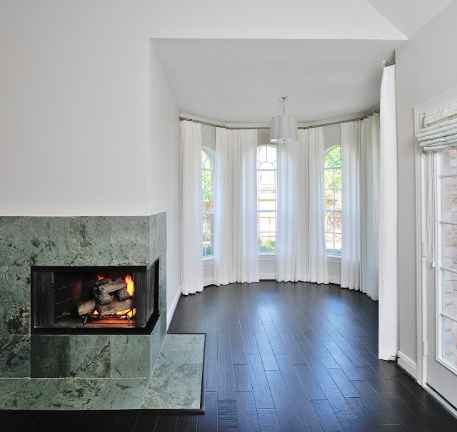 These windows were different sizes and made the space feel choppy. With a solid wall of drapery, it appears soft and cohesive.  Carla Aston, Designer   #baywindow #archedwindows