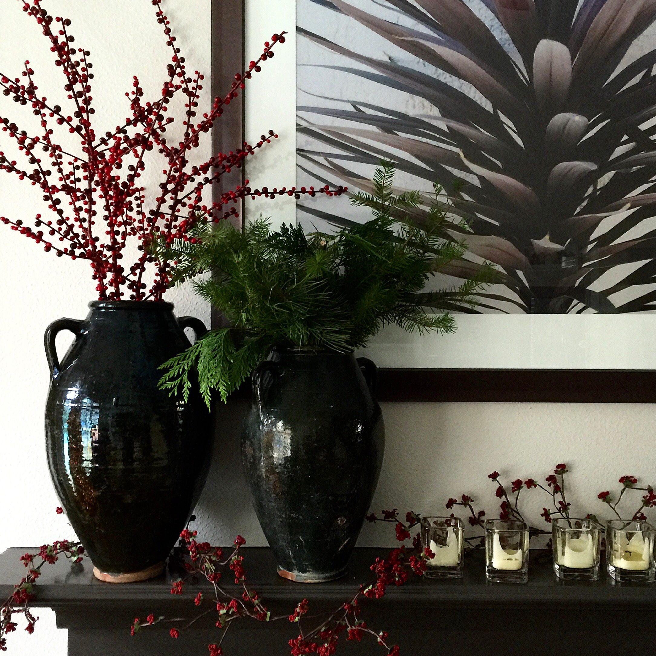 Rustic holiday mantel decor with antique olive jars