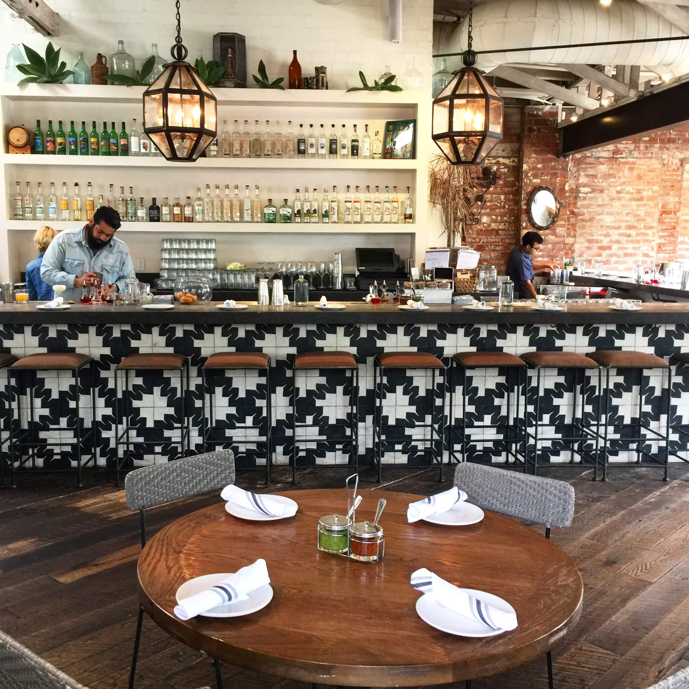 Black and white graphic tile bar face, rustic wood floor | Gracias Madre - Los Angeles