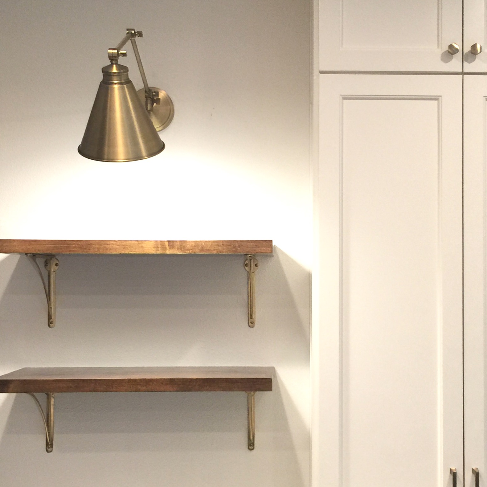 open shelving with brass brackets and brass sconce